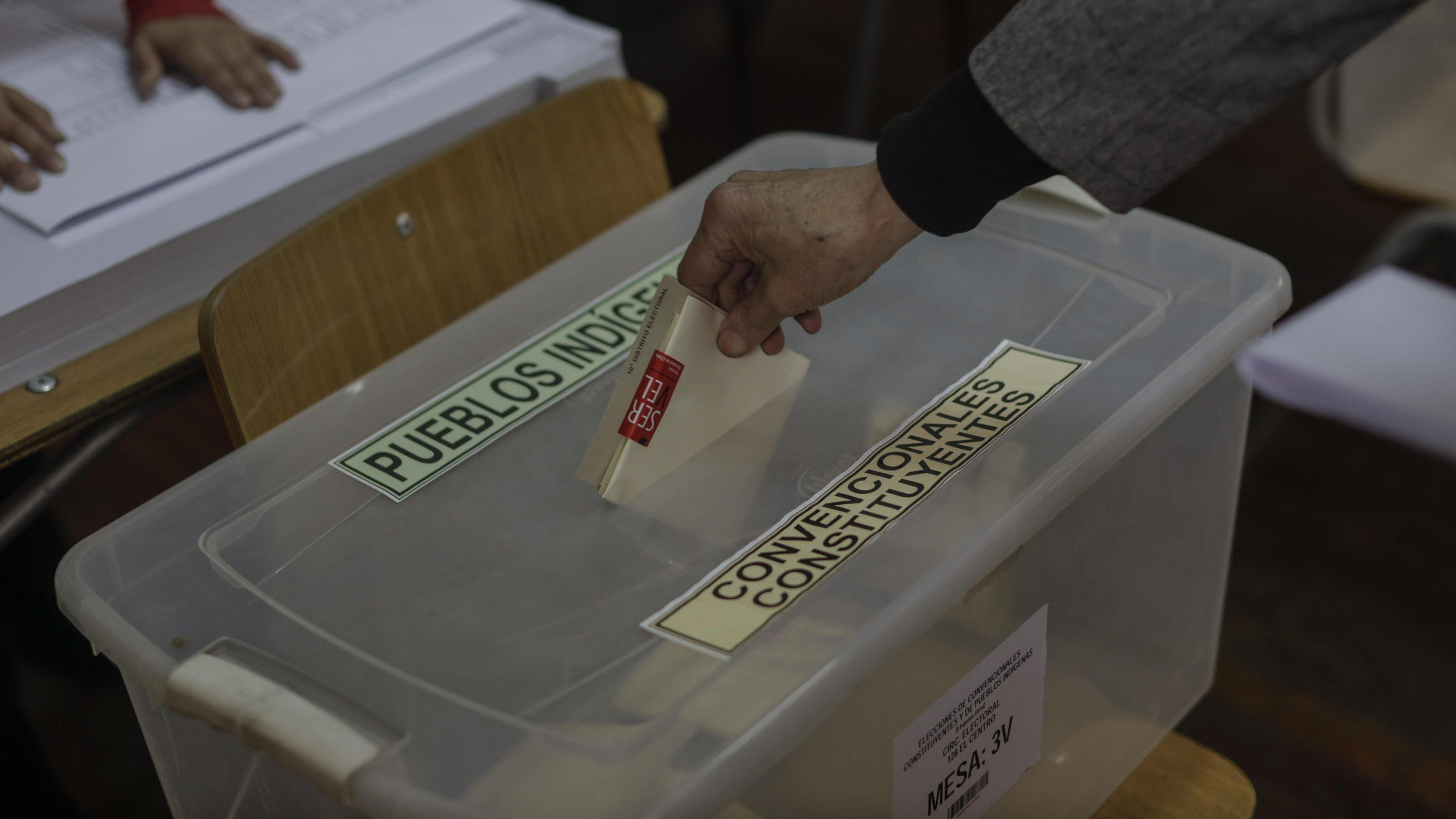 Jemand wirft seinen Stimmzettel in eine Wahlurne.