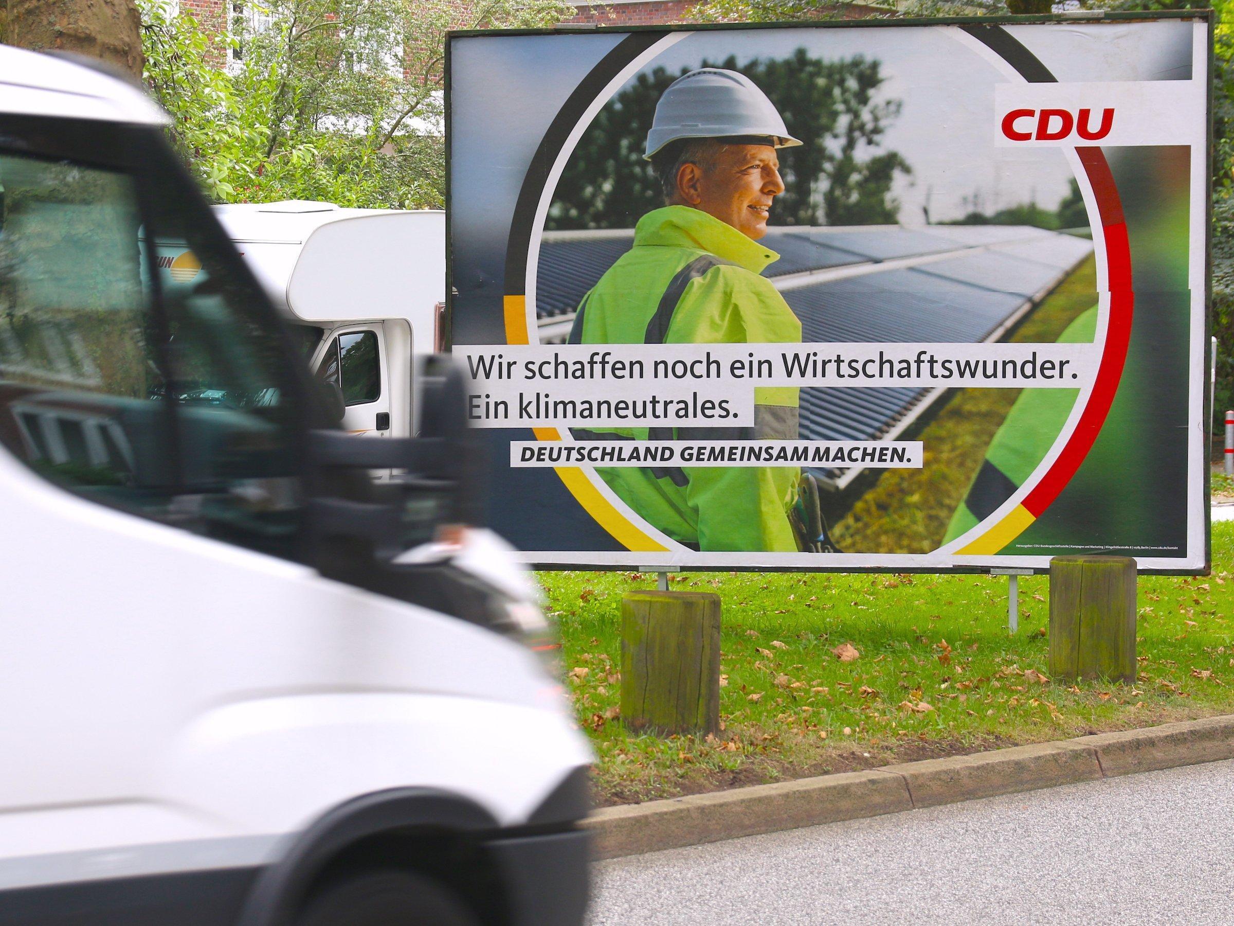 """Ein Wahlplakat der CDU zeigt einen Mann mit Bauarbeiterhelm und neongelbem Anorak vor einer Reihe von Solarpanels. Der Slogan lautet: """"Wir schaffen noch ein Wirtschaftswunder. Ein klimaneutrales."""" Das Plakat steht auf einem Grünstreifen an der Straße. Von links fährt ein weißer Kleinlaster ins Bild."""