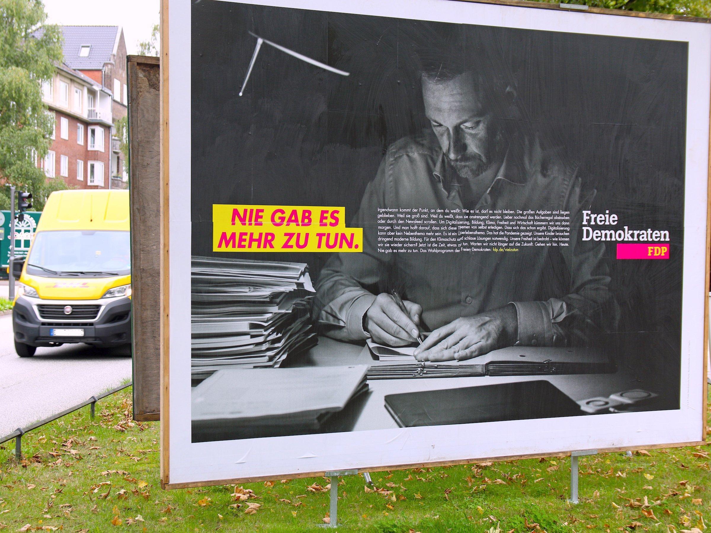 """Wahlplakat der FDP: Partei-Chef Christian Lindner sitzt nachts am Schreibtisch und macht Notizen in einer Kladde. Neben ihm auf dem Schwarz-Weiß-Foto liegt ein Stapel Aktendeckel. Der Slogan in geblockten Buchstaben auf gelbem Grund ist: """"Nie gab es mehr zu tun"""". Das Plakat steht auf einem Grünstreifen, links fährt ein gelber Lieferwagen vorbei."""