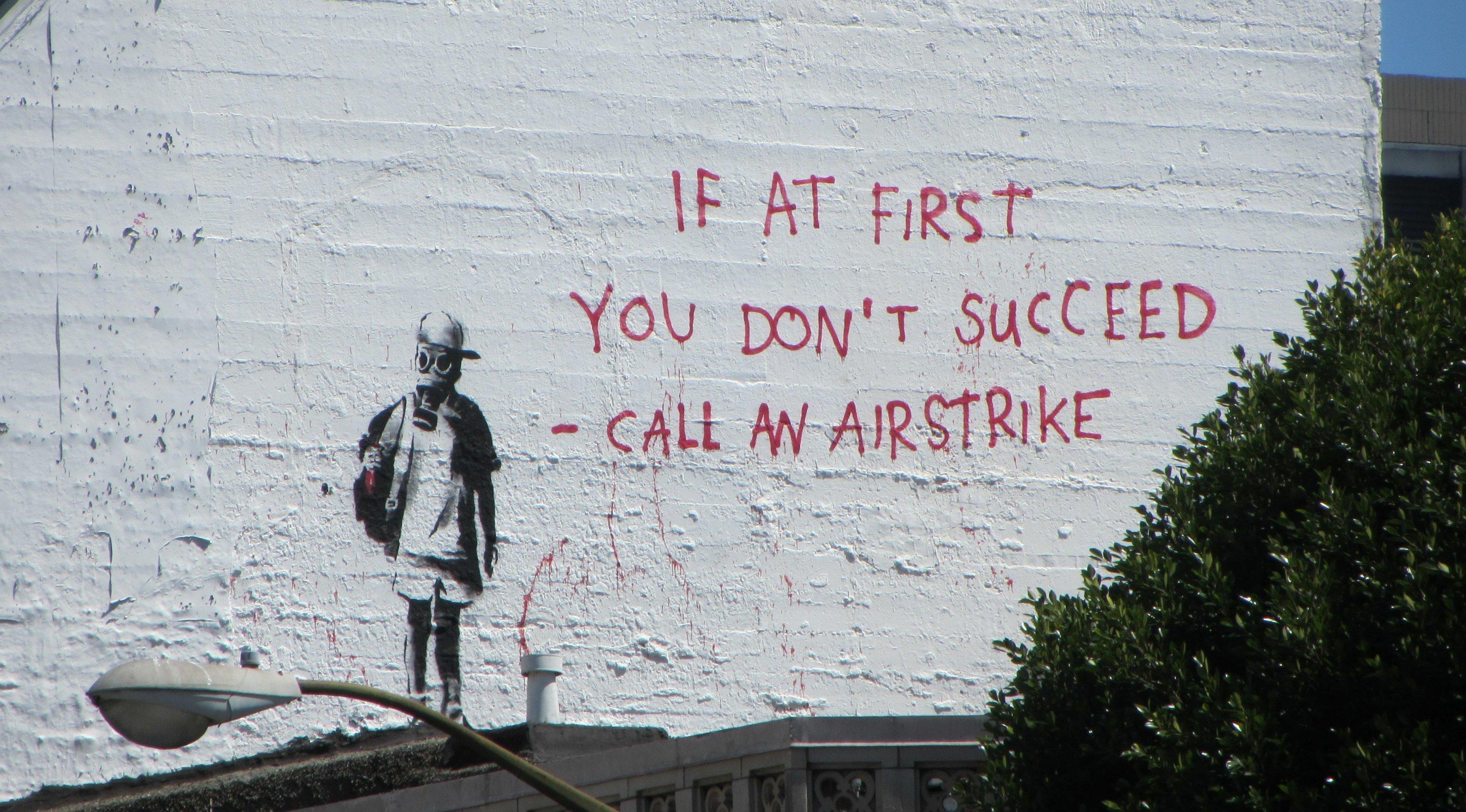 """Auf einer Wand ist eine Figur mit Gasmaske gemalt. Daneben der Spruch: """"If at first you don't succeed, call an airstrike."""""""