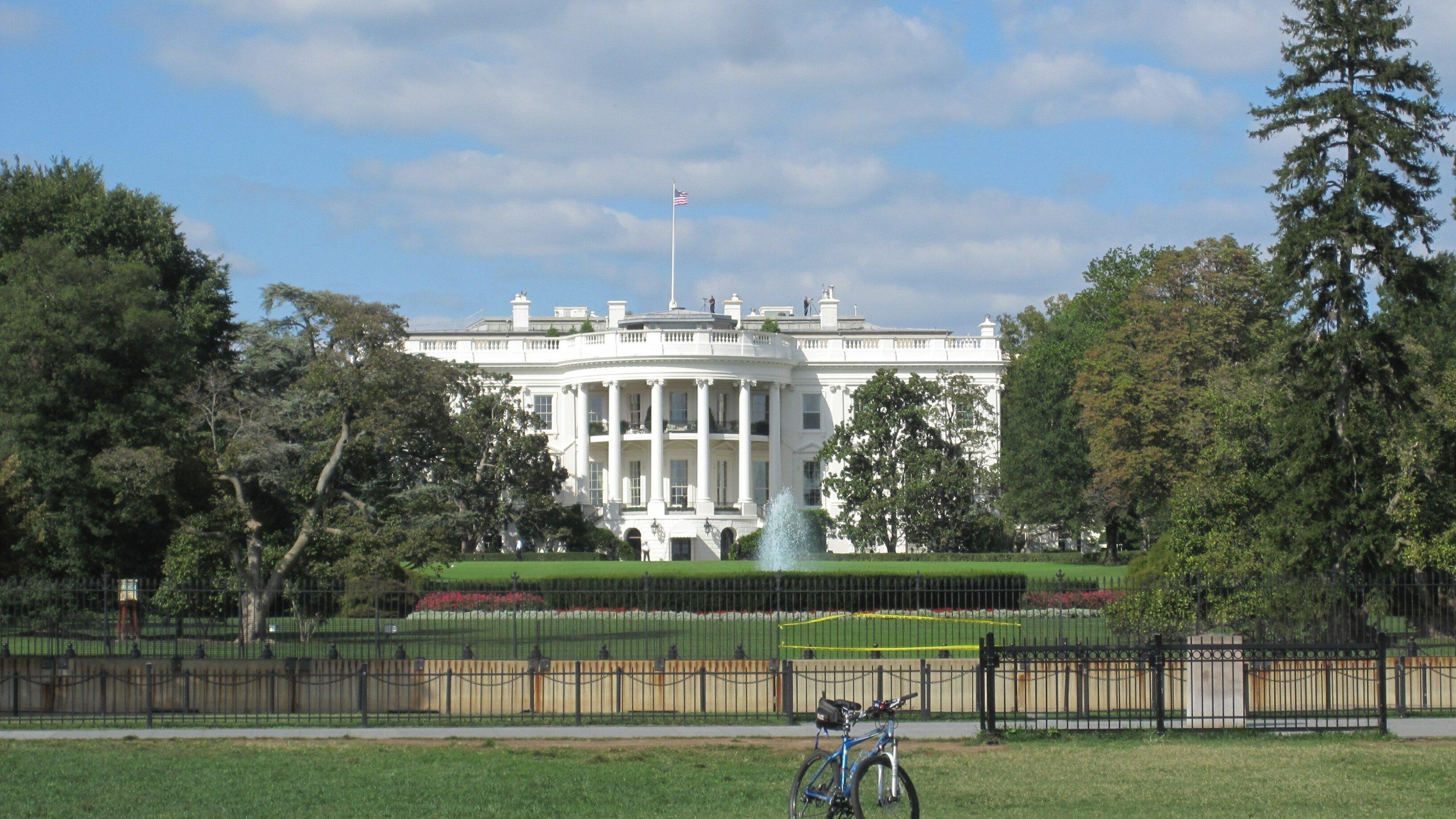 Blick aufs Weiße Haus in Washington D.C. Im Vordergrund parkt ein Fahrrad auf dem Rasen.