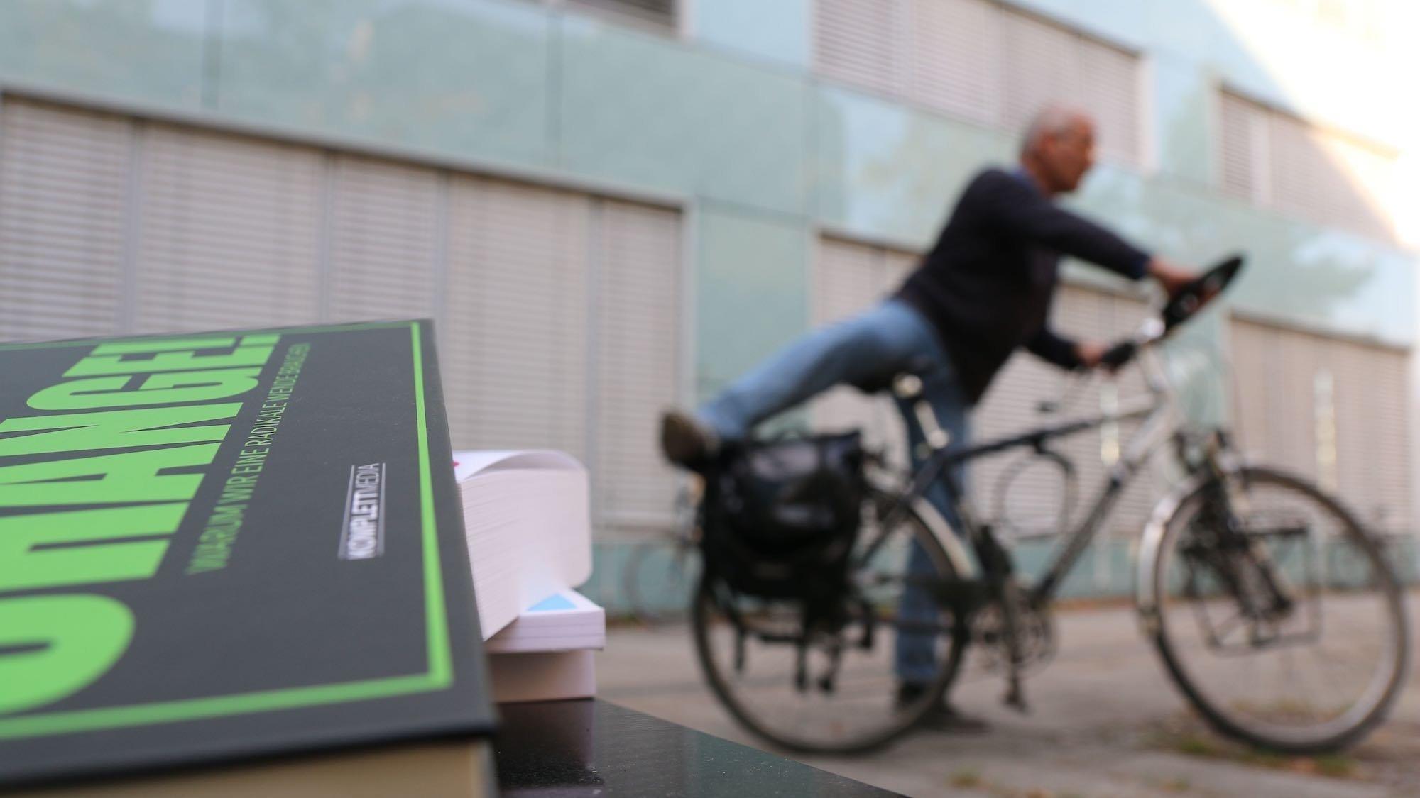 Symbolbild von Wissen zum Handeln. Im Vordergrund liegt ein Stapel Bücher über die nötige Transformation, im Hintergrund steigt ein Mann auf das Fahrrad