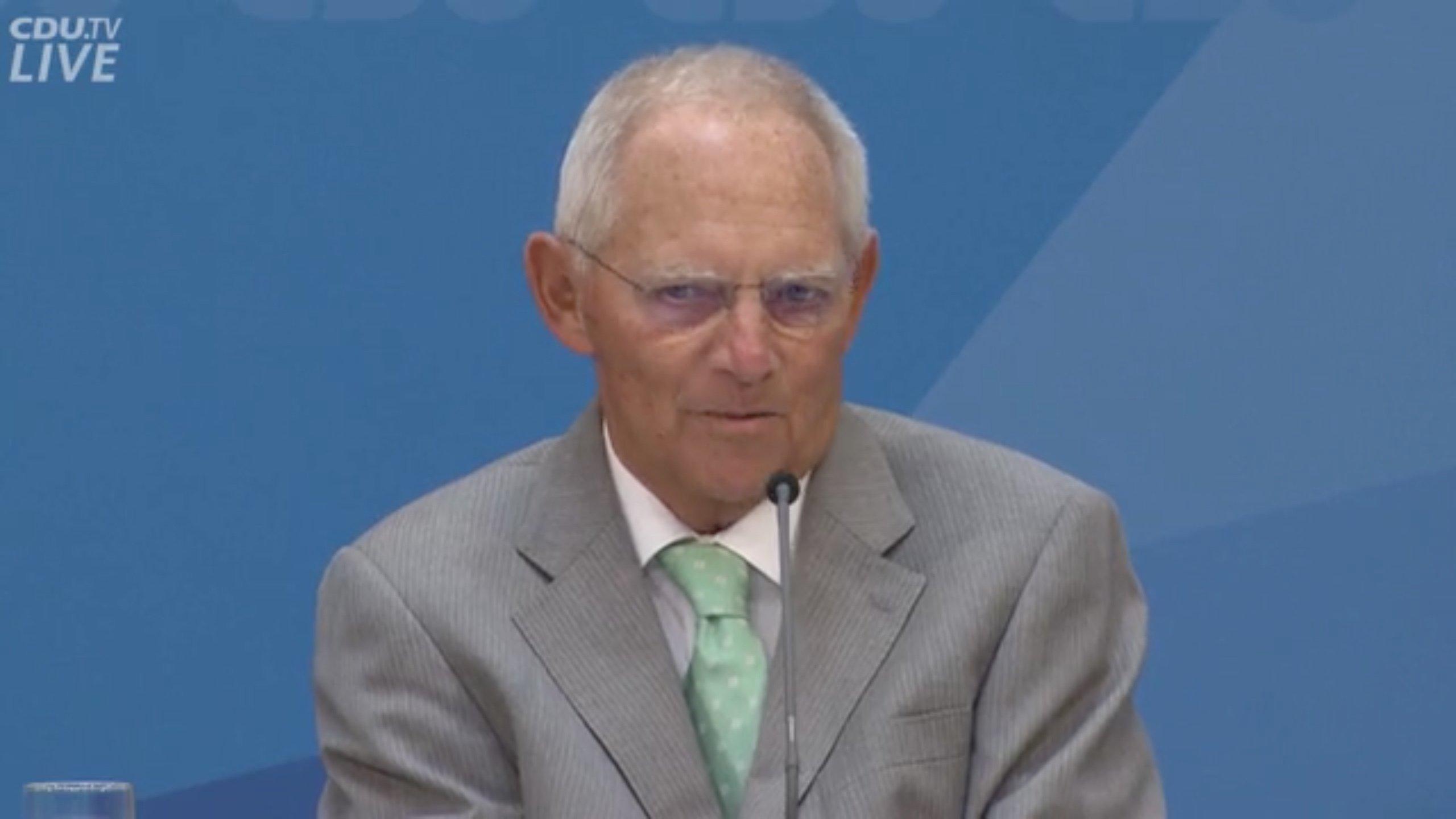 """Wolfgang Schäuble, Bundestags-Präsident und CDU-Mitglied bei einer Rede. Er trägt einen grauen Anzug und sitzt vor einem blauen Hintergrund. – """"Lieber ein nicht perfekter Schritt in die konkrete Richtung, als auf der Suche nach der perfekten Lösung am Ende gar nichts zu machen.""""  Wolfgang Schäuble redete seiner Partei bei deren Werkstattgespräch Anfang September 2019ins Gewissen. Sie solle endlich mal mit dem Klimaschutz anfangen, meinte er und fügte mit sichtlicher Freude – die eigenen Fremdsprachenkenntnisse karikierend – hinzu: """"Second bescht ist allemal besser als nossing."""""""