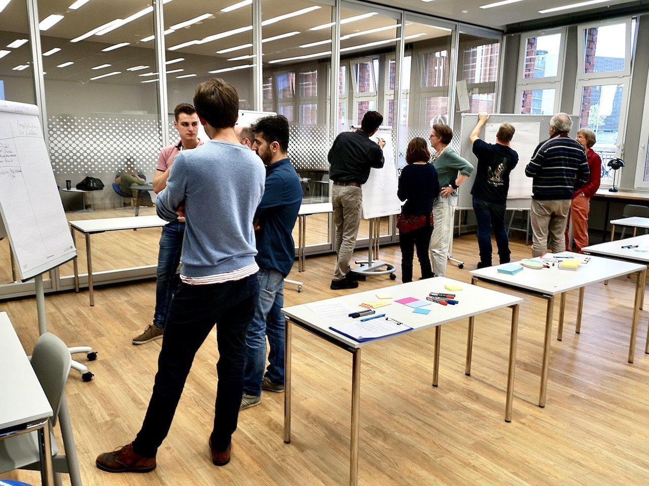 Arbeitsphase in der Hamburger Zentralbibliothek: Vier Gruppen stehen vor den Stellwänden und diskutieren