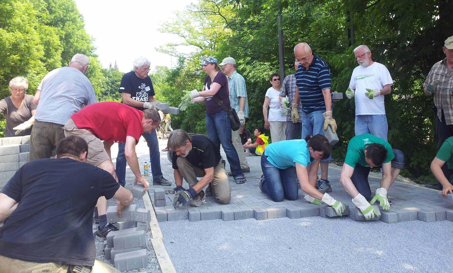 Eine Gruppe von mittelalten bis alten Menschen pflastern gemeinsam einen Weg.