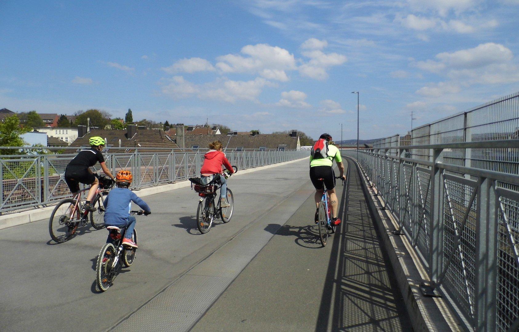 Vier junge Personen fahren unter blauem Himmel mit ihrem Rad über die Brücke.