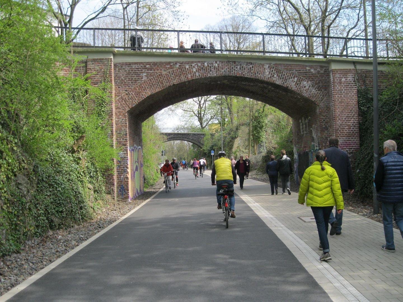 Unter einer Fußgängerbrücke herrscht reger Verkehr: Viele Fußgänger und Radfahrer sind hier unterwegs.