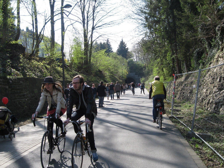 Zwei Radfahrer im Vordergrund. Im Hintergrund sind vor allem Fußgänger zu sehen, aber auch ein Skater und ein weiterer Radfahrer.