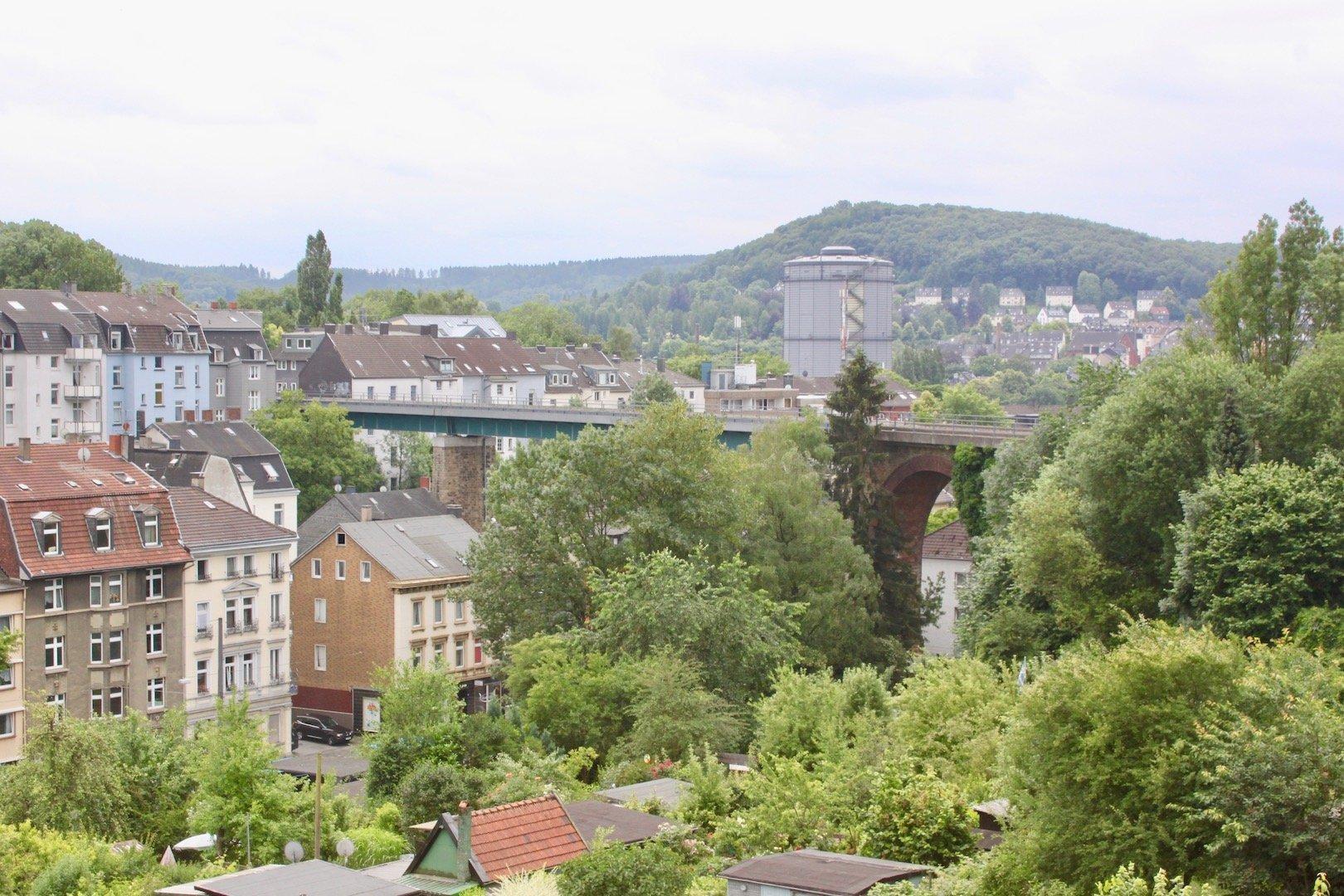 Blick auf Wuppertal von einem hohen Punkt: Neben Häusern sind vor allem grüne Bäume zu sehen.