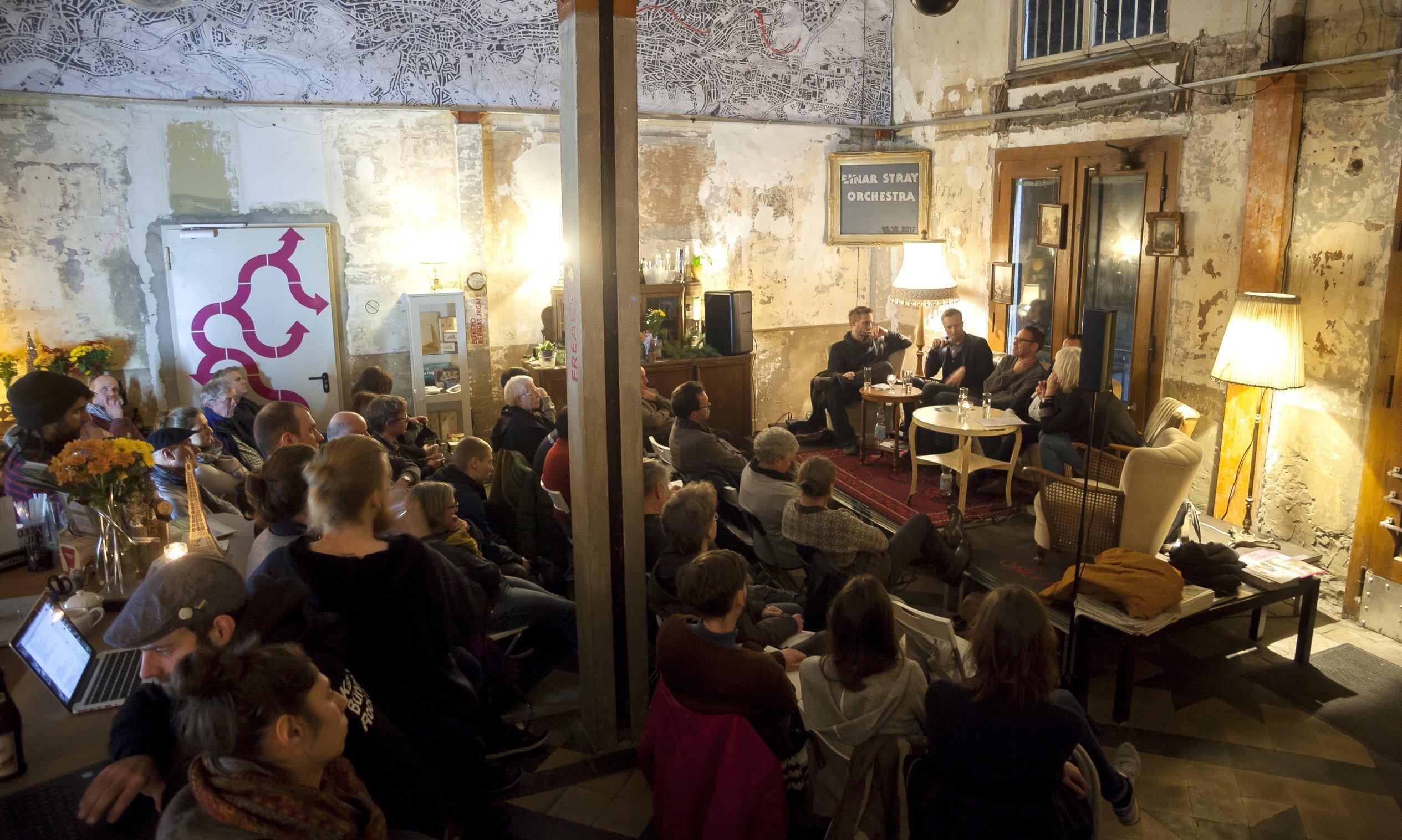 Blick in einen Raum ohne Tapeten, in dem viele Zuschauer vor einer kleinen Bühne sitzen. Darauf diskutieren fünf Menschen.