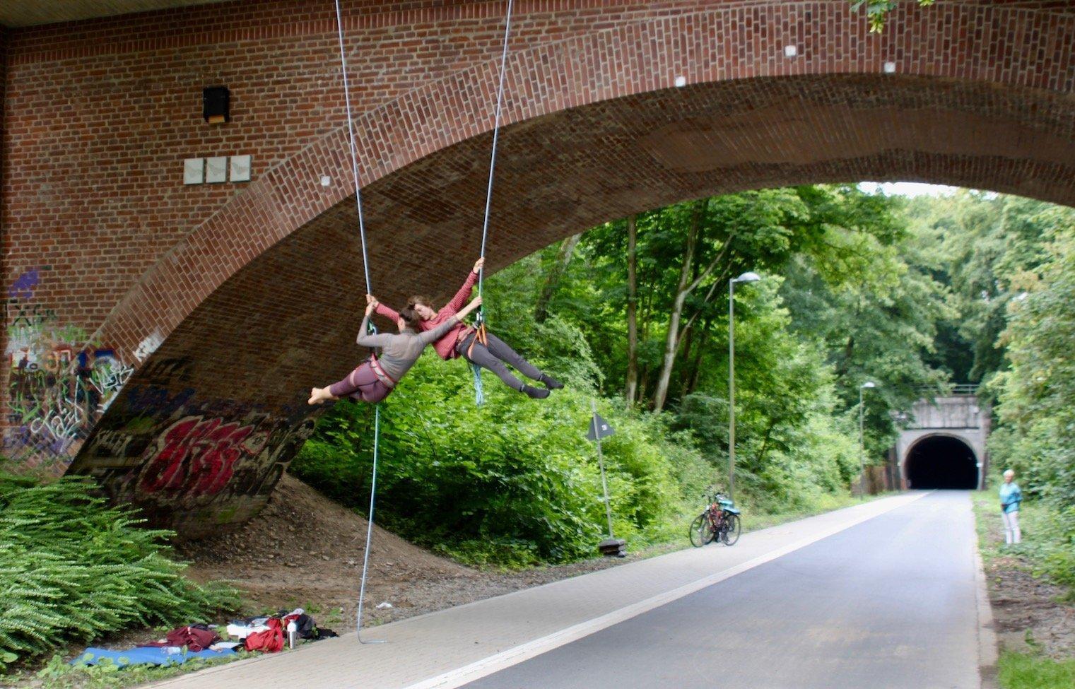 Zwei Menschen seilen sich an einer Brücke ab. Unter ihnen ist ein leerer Fußweg und ein schmaler Radweg.