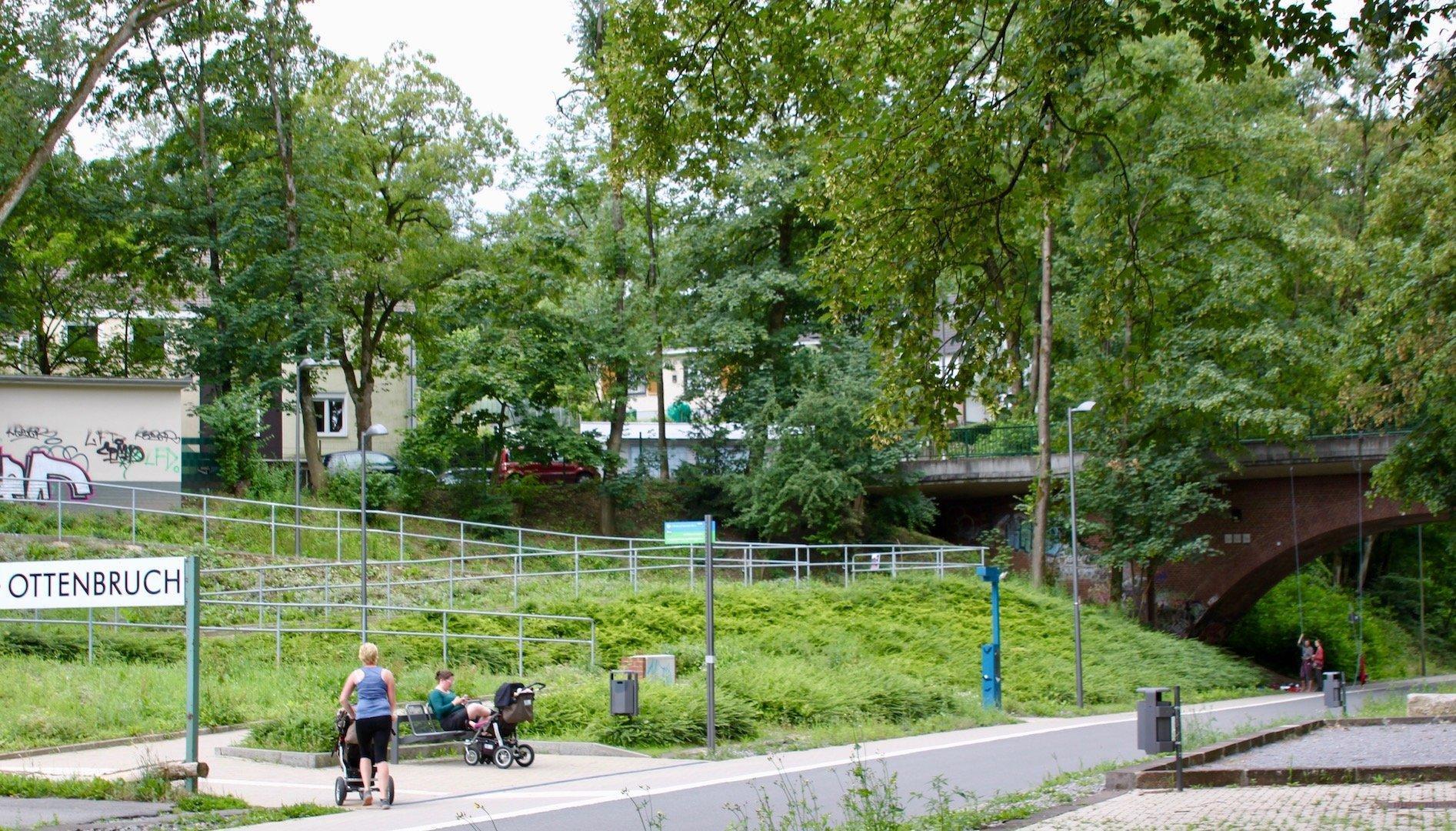An der Trasse ist viel grünes Buschwerk zu sehen. Zwei Menschen mit Kinderwägen sind zu sehen.