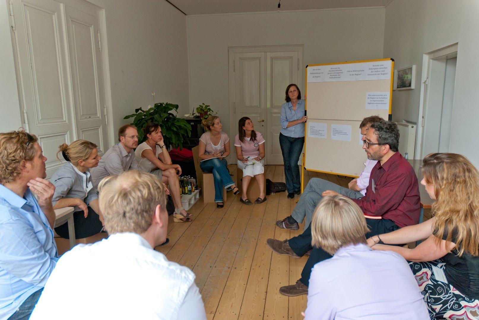 Teilnehmer des Workshops in einem kleinen Raum mit weißen Wänden und hellem Bretterboden.