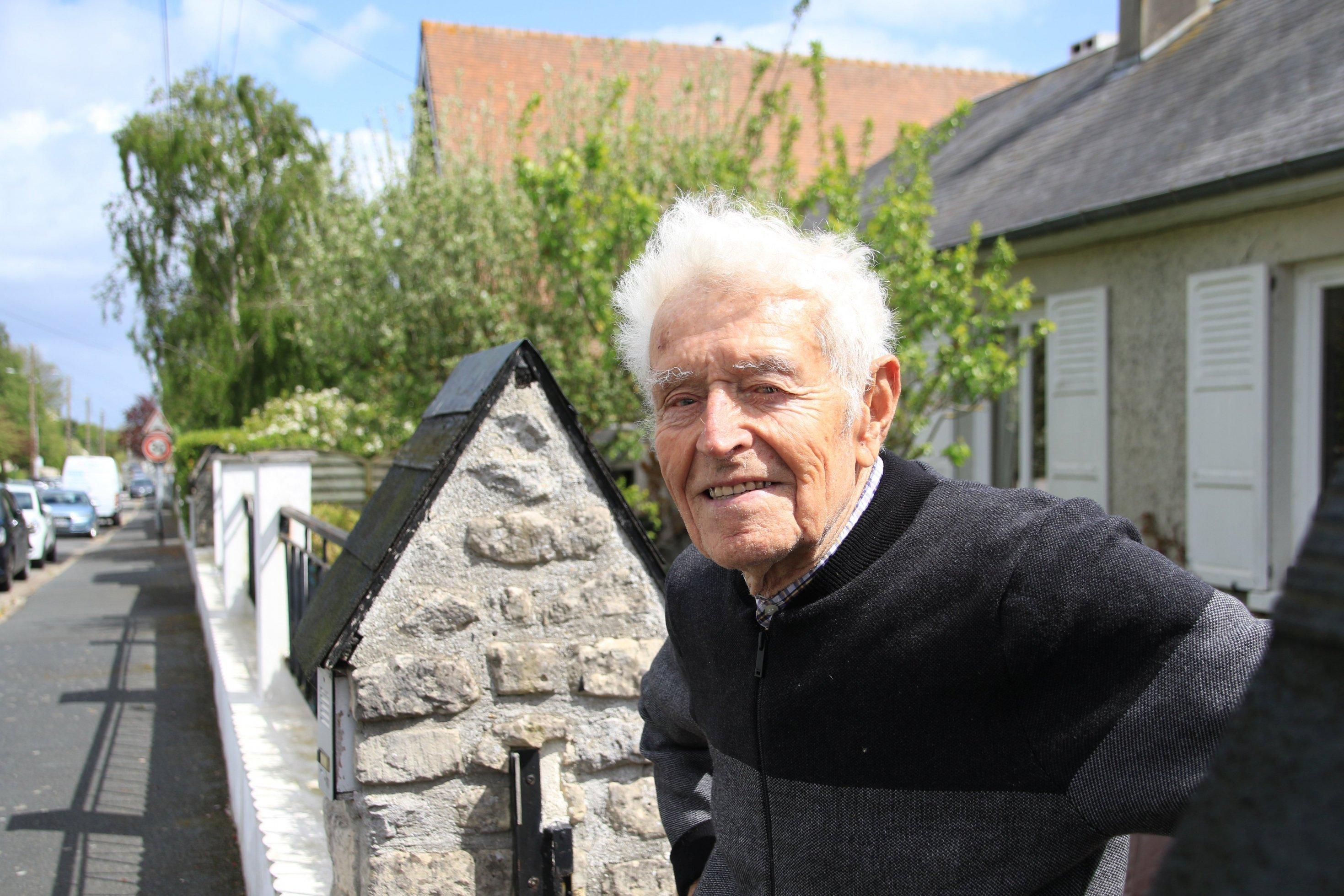 Ein alter Mann in einem Vorgarten