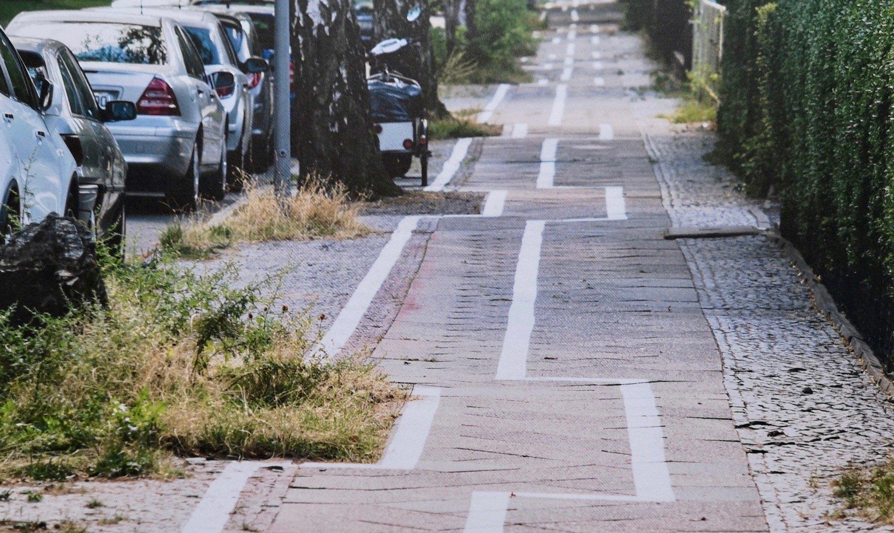 Blick auf einen Radweg mit einem zickzack-ähnlichen Pflastermuster.