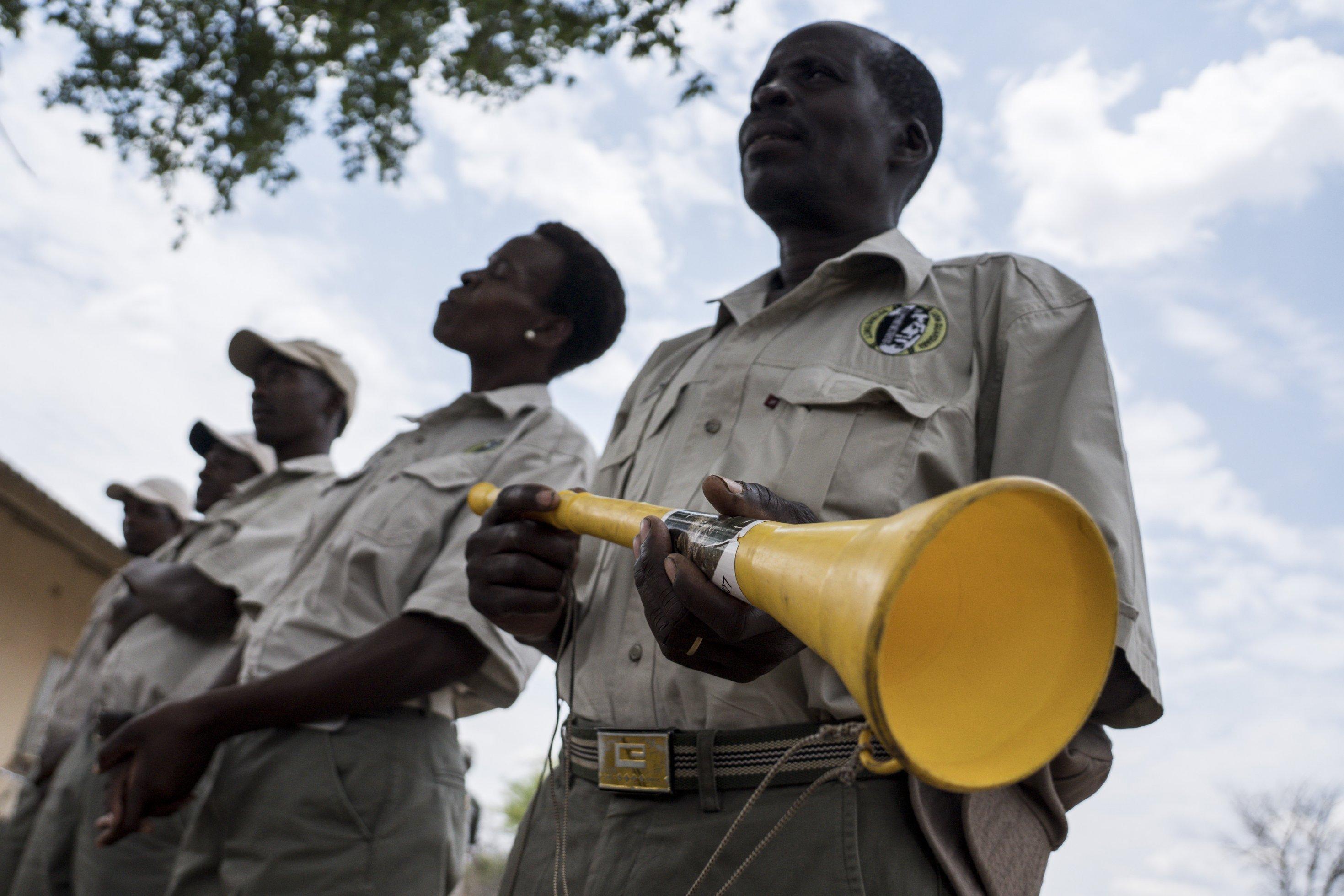 Die Lion Guardians stehen in einer Reihe, der Mann im Vordergrund hält eine Vuvuzela, eine gelbe Plastiktröte in den Händen