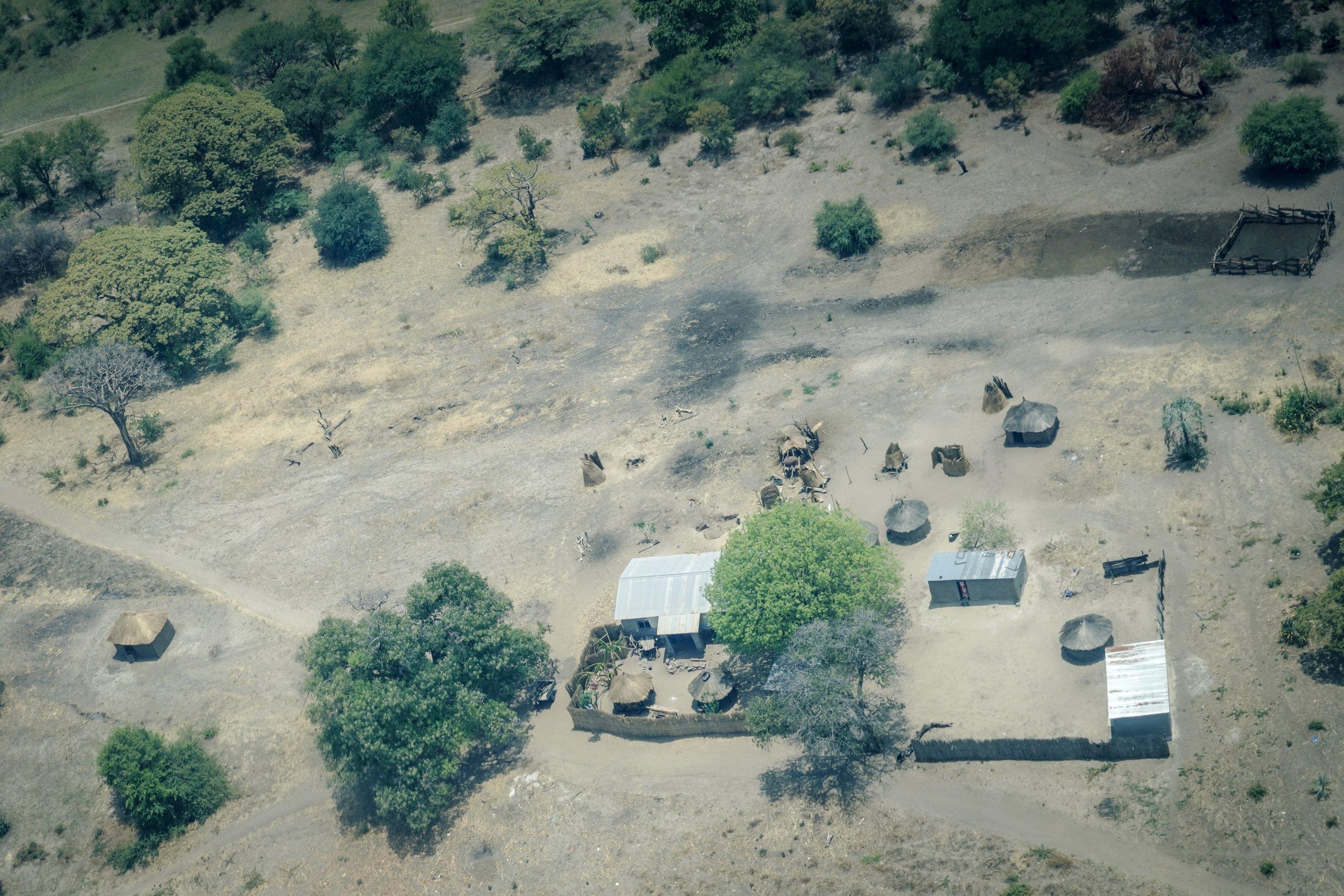 Die Aufnahme aus der Luft zeigt ein paar Gebäude und Rundhütten, einen Zaun und drumherum eine weite Ebene mit ein paar Bäumen