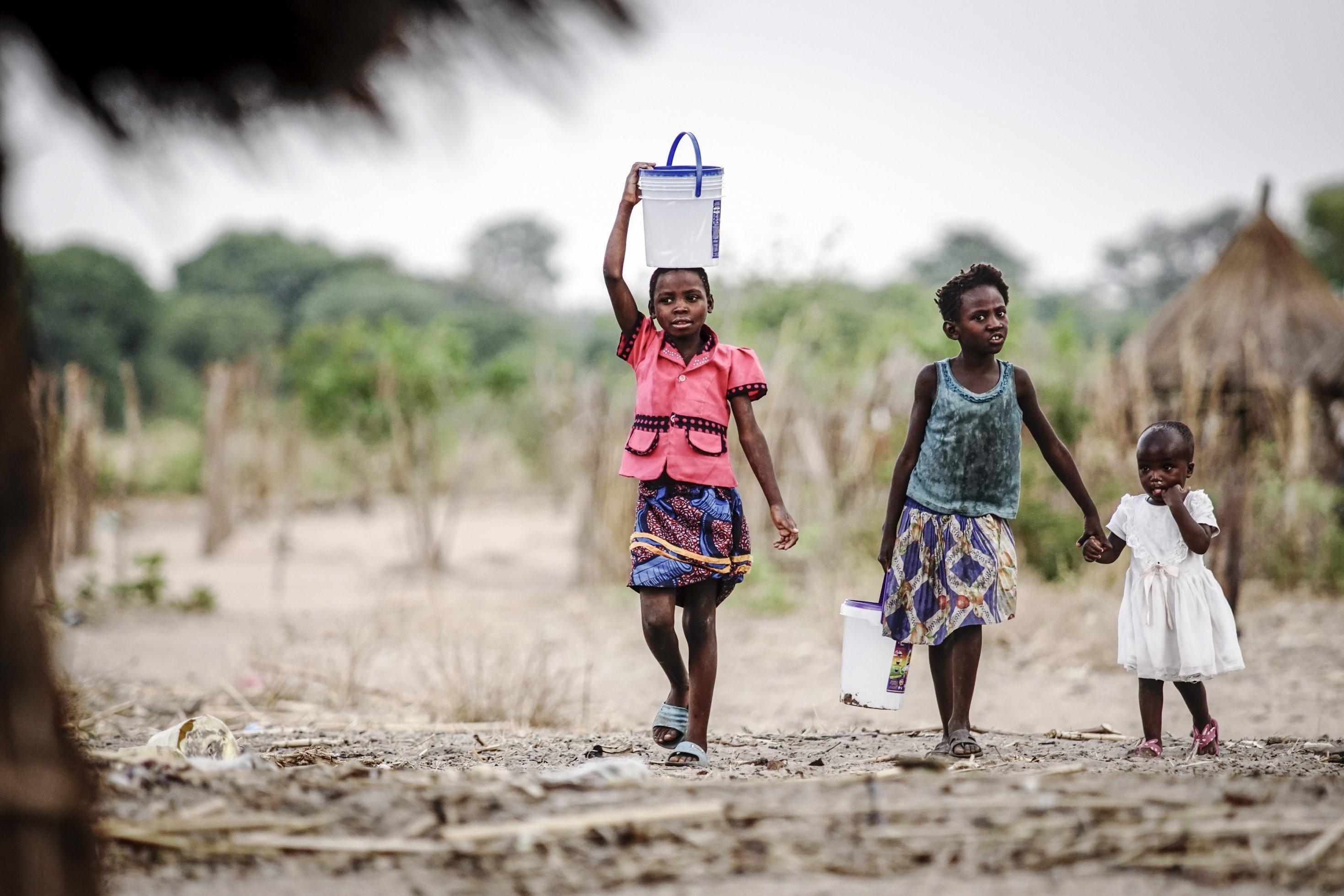 Zwei Mädchen tragen Eimer mit Wasser, eine hat ihn auf dem Kopf, die andere hält ein kleineres Mädchen an der Hand