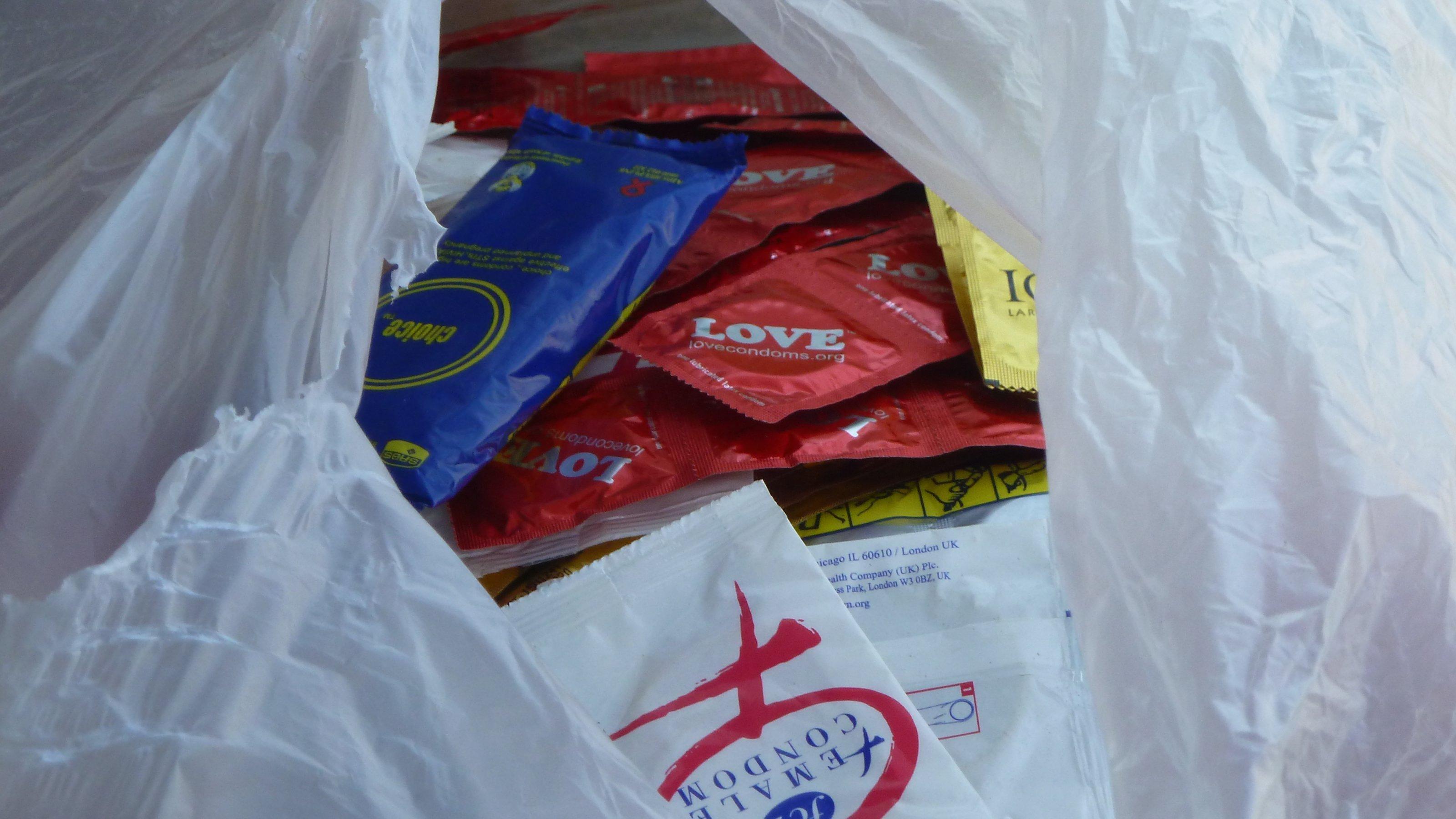 Zu sehen ist eine halb aufgerissene, weiße Tüte, in der Kondome in unterschiedlichen Verpackungen für die Verteilung bereitliegen.