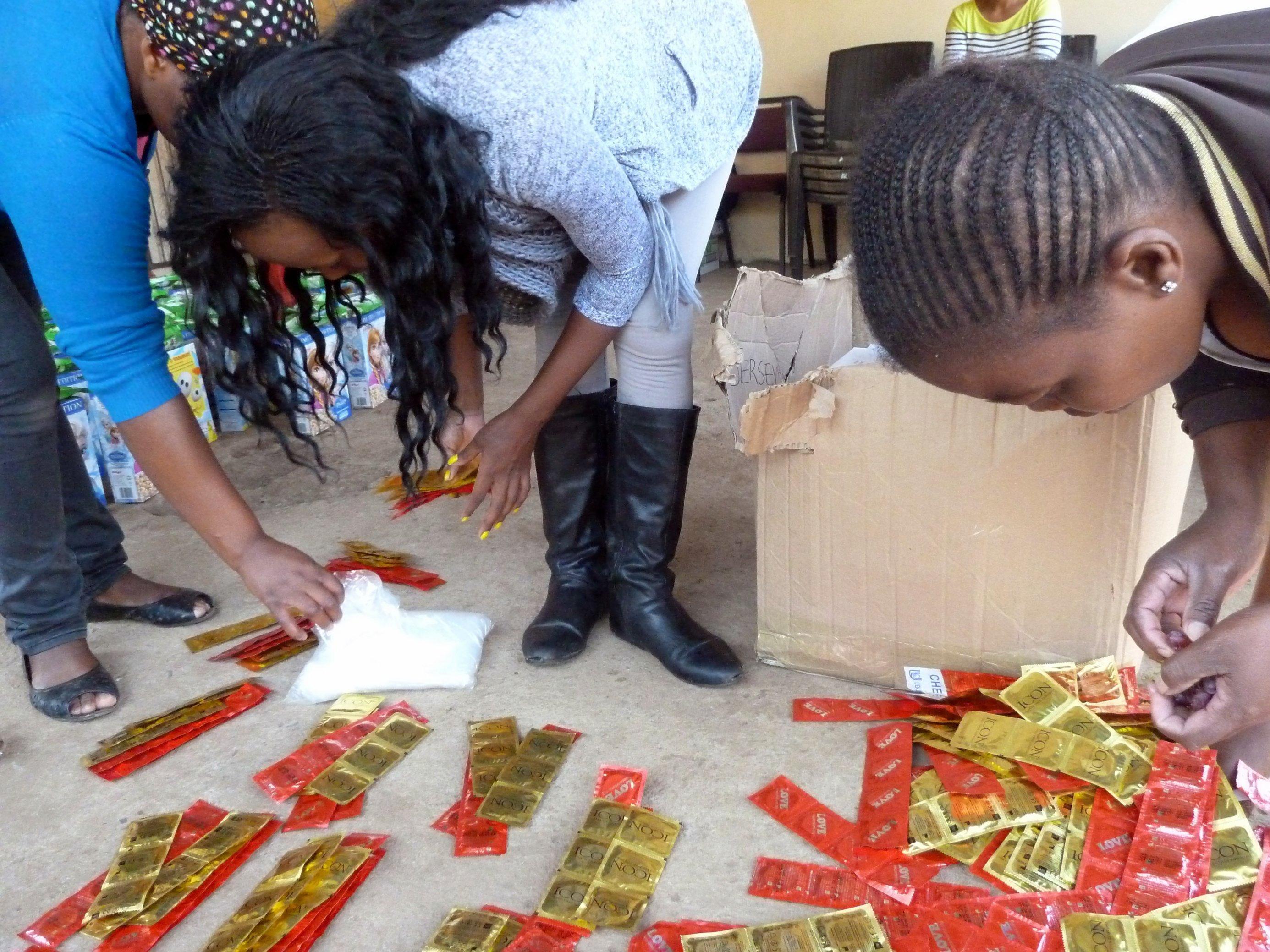 Aktivistinnen beugen sich über verpackte Kondome, die auf dem Boden liegen, um sie für die Verteilung zurechtzulegen.