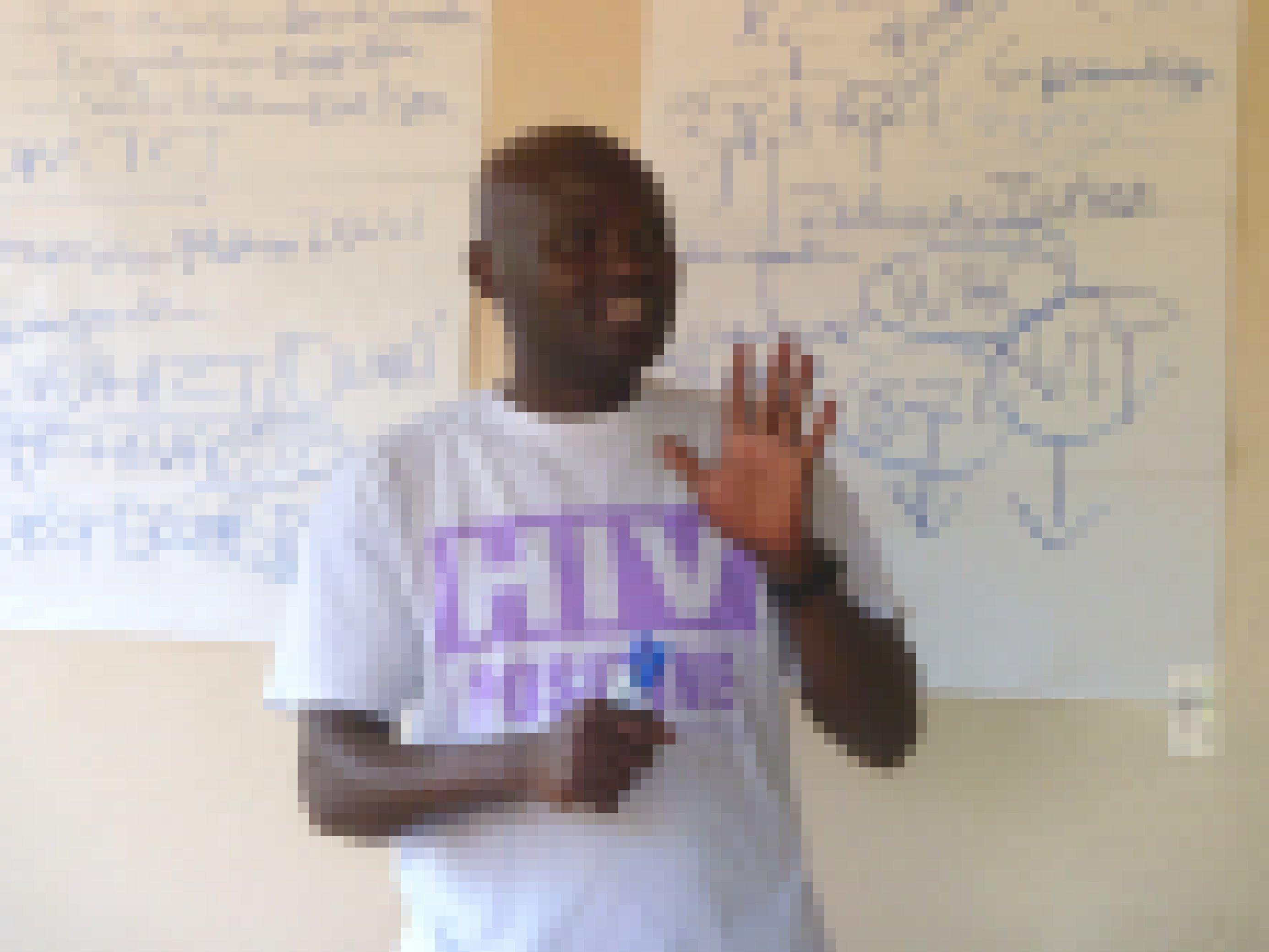 Ein Aktivist mit einem T-Shirt, der Aufdruck: HIV positiv. Er steht vor einer Tafel und gestikuliert, hält offensichtlich gerade einen Vortrag.