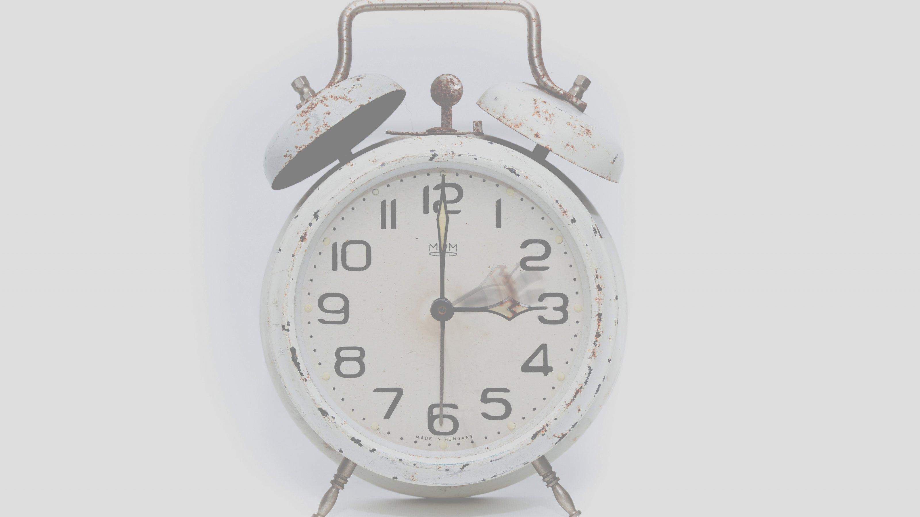 Ein Wecker, dessen Zeiger von zwei auf drei Uhr vorgestellt werden.