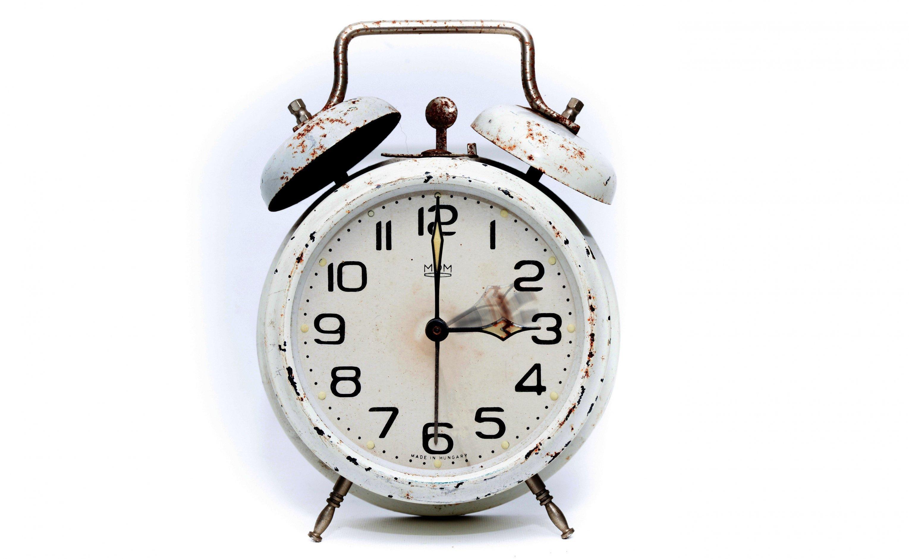 Ein Wecker, bei dem die Zeiger von zwei auf drei Uhr vorgestellt werden.