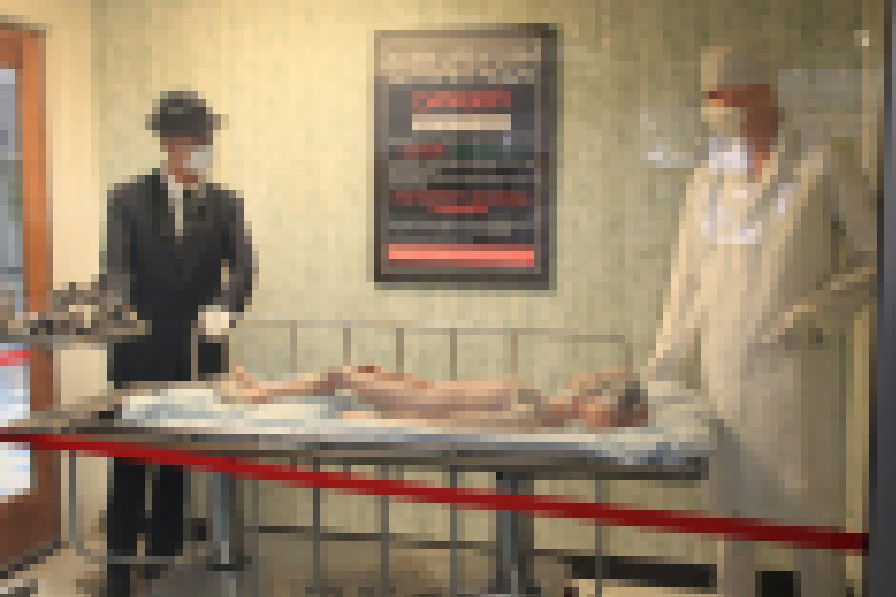 Zwei Männer mit Masken beugen sich über ein Krankenbett, in dem ein Alien liegt.