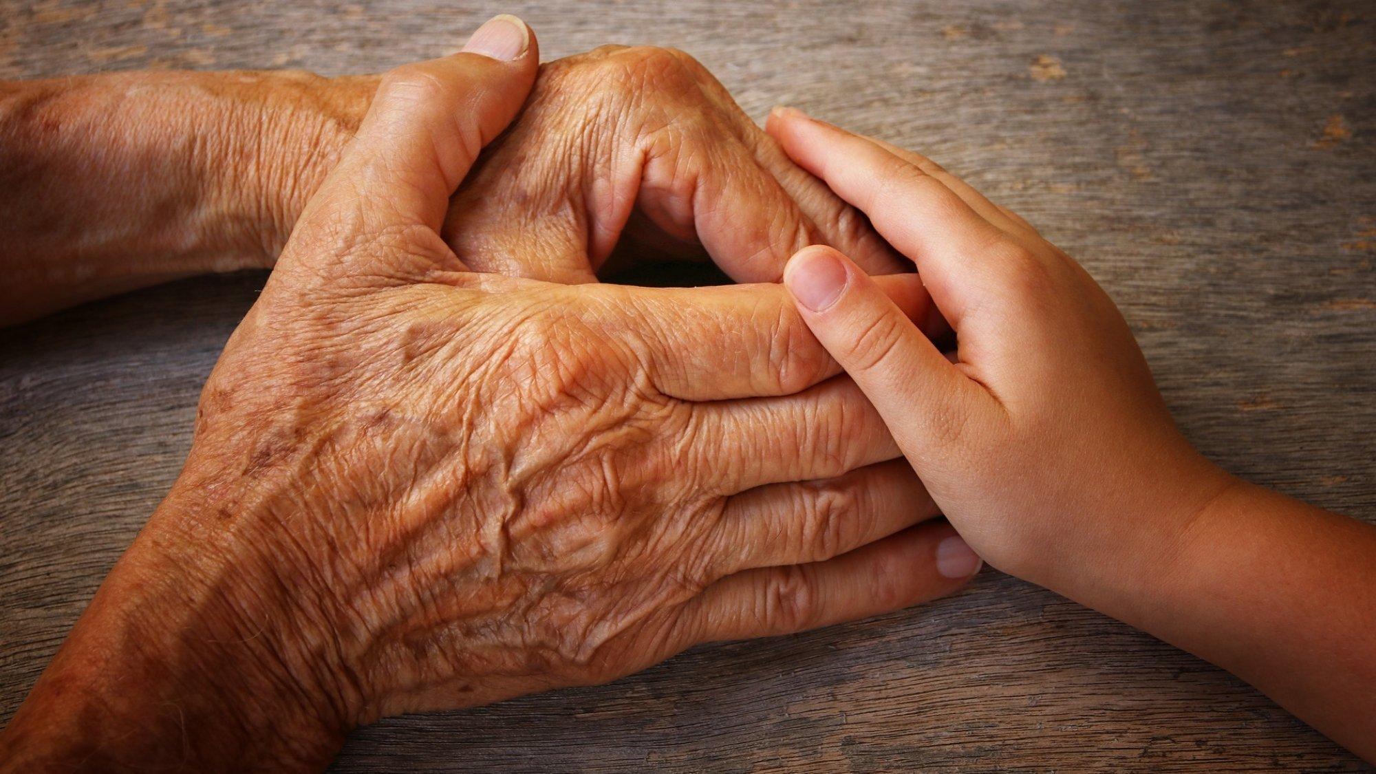 Foto von der Hand eines alten Mannes, der die Hand eines Kindes hält.