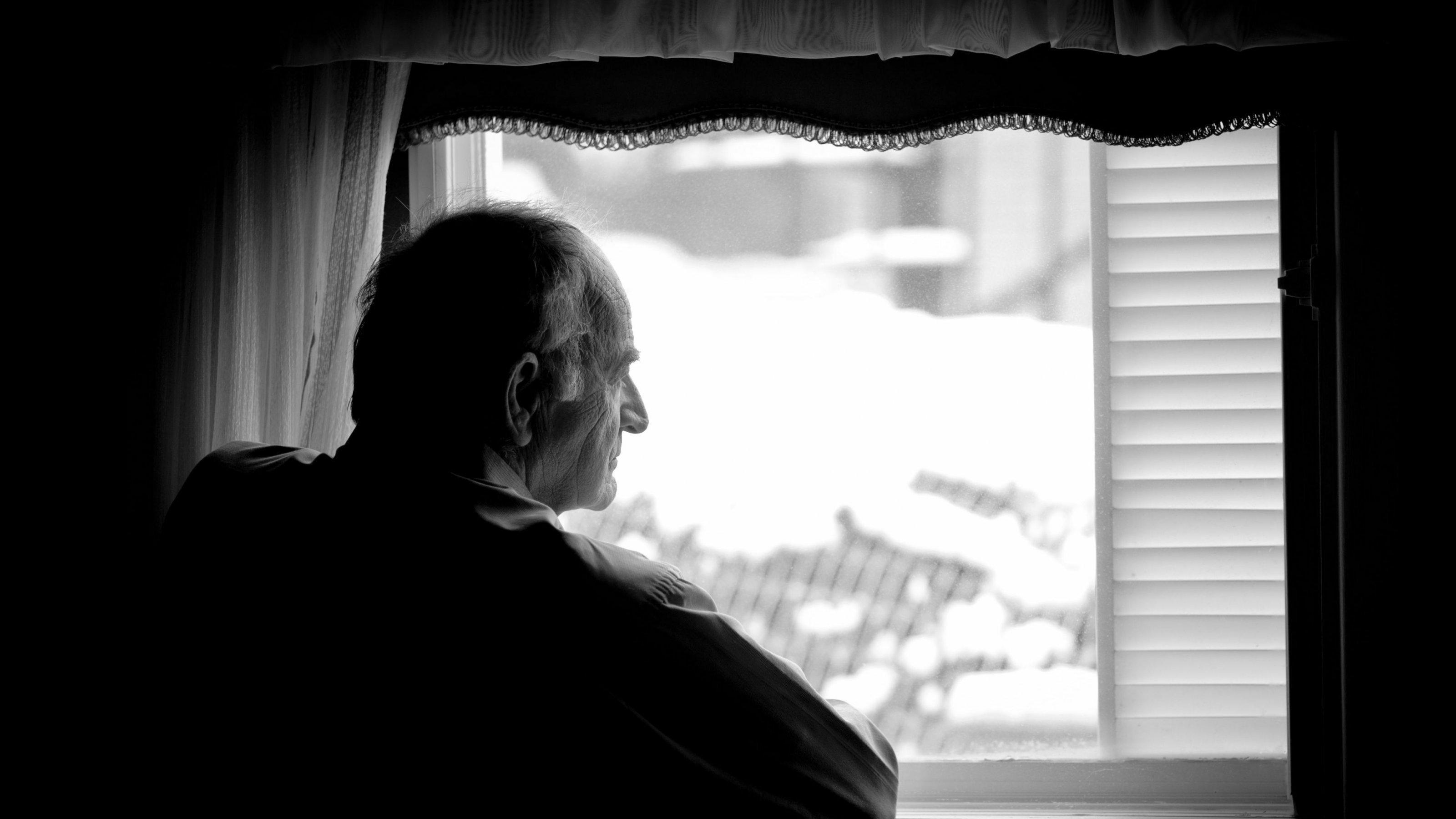 Alter Mann schaut aus dem Fenster. Während der Corona-Pandemie bedeutet Schutz oft Isolation der Risikogruppen.