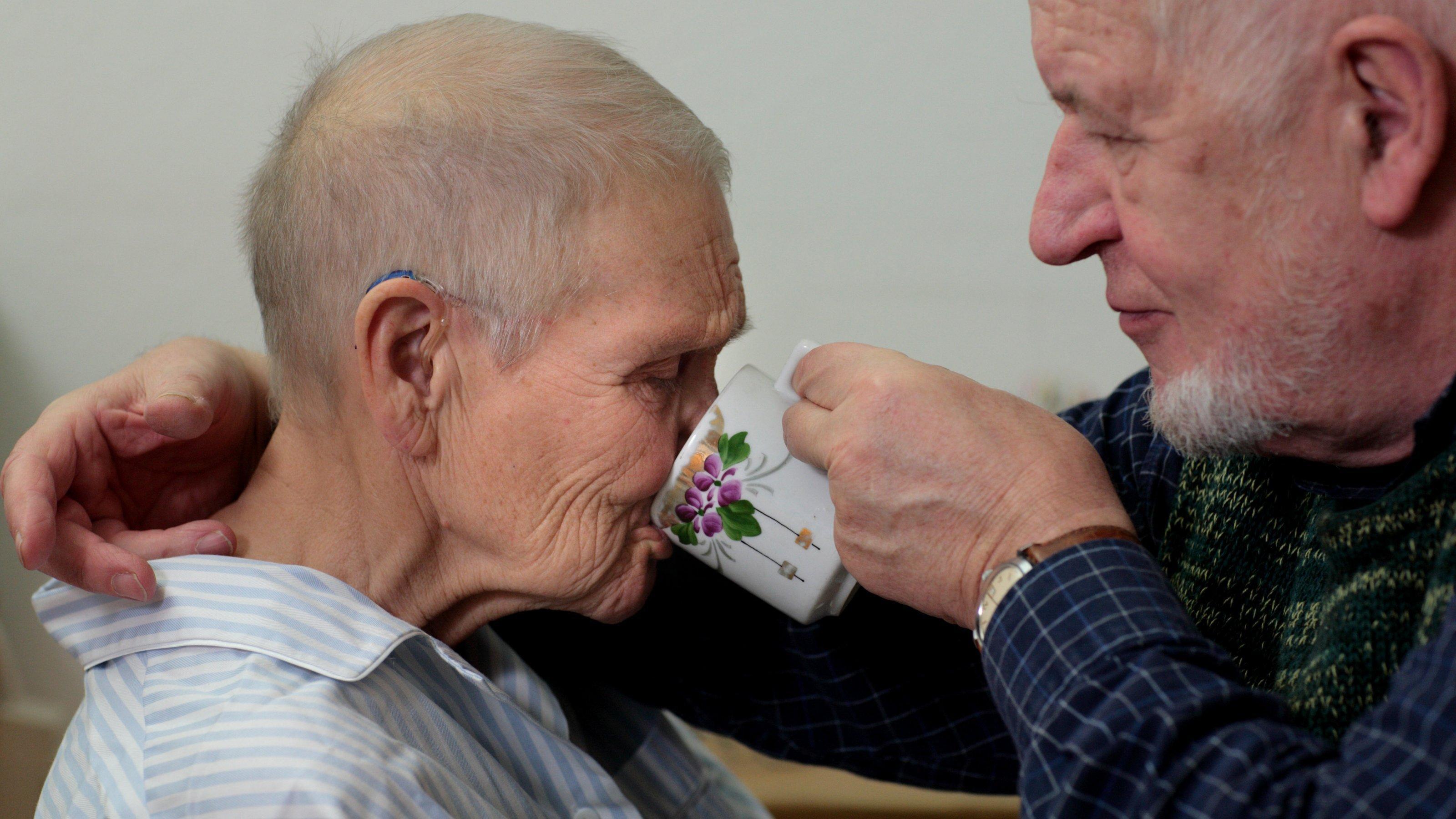 Ein alter Mann hilft seiner Frau beim Trinken, 80Prozent der Pflegebedürftigen werden von Angehörigen versorgt.