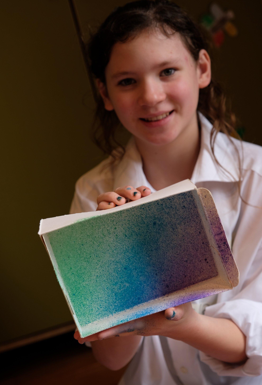 Die zwölfjährige Alva zeigt einen leeren Karton. Innen ist er bunt von grün über blau bis violett, alles kleine Spritzer, die sie mit der Spritztechnik verteilt hat.