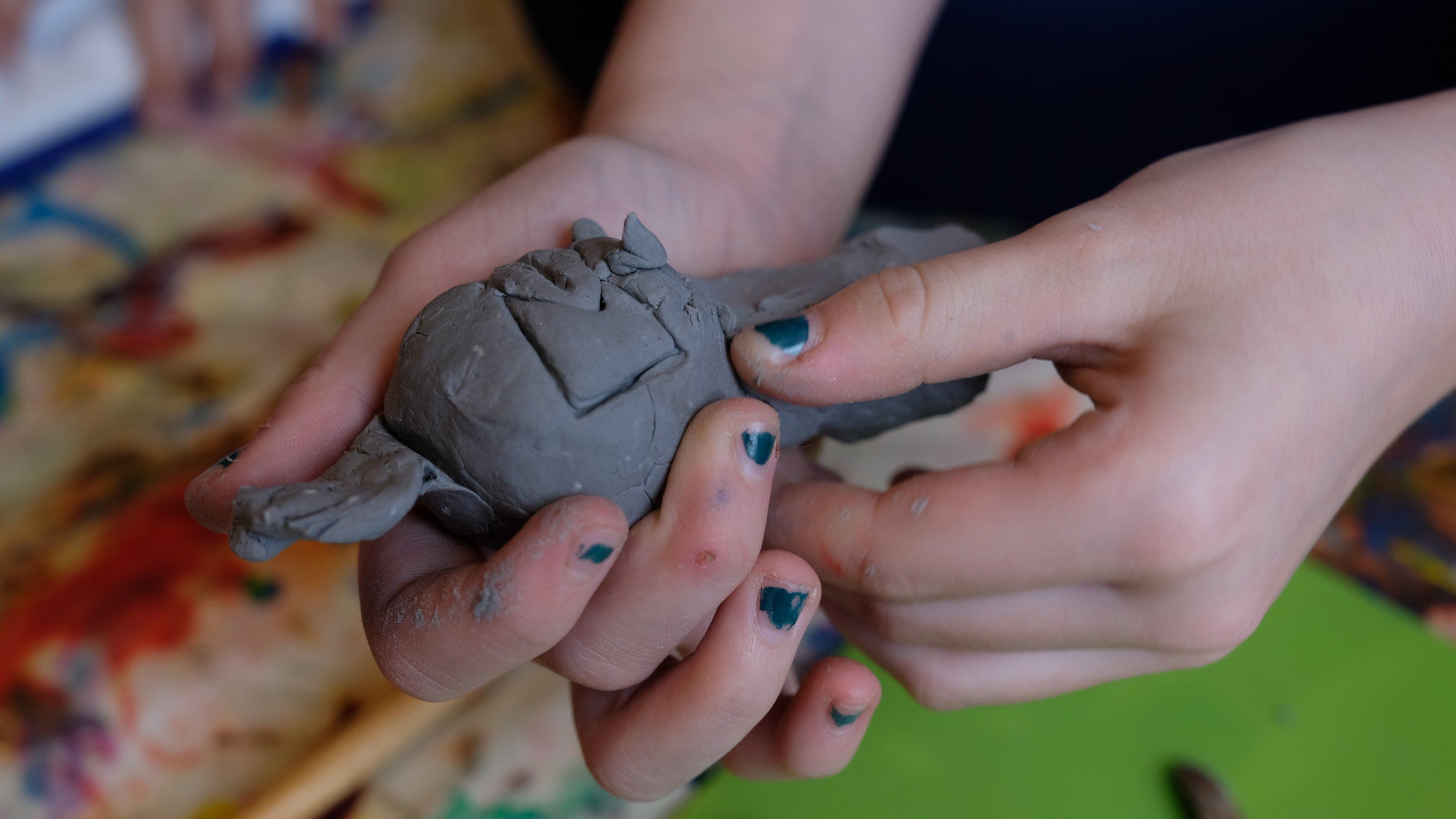 Man sieht ganz nah die beiden Hände von Alva, wie sie aus Ton eine Phantasiefigur kneten. Darunter sieht man unscharf eine grüne Unterlage, die sie zum Arbeiten benutzt, ein paar Werkzeuge und viele Farben.