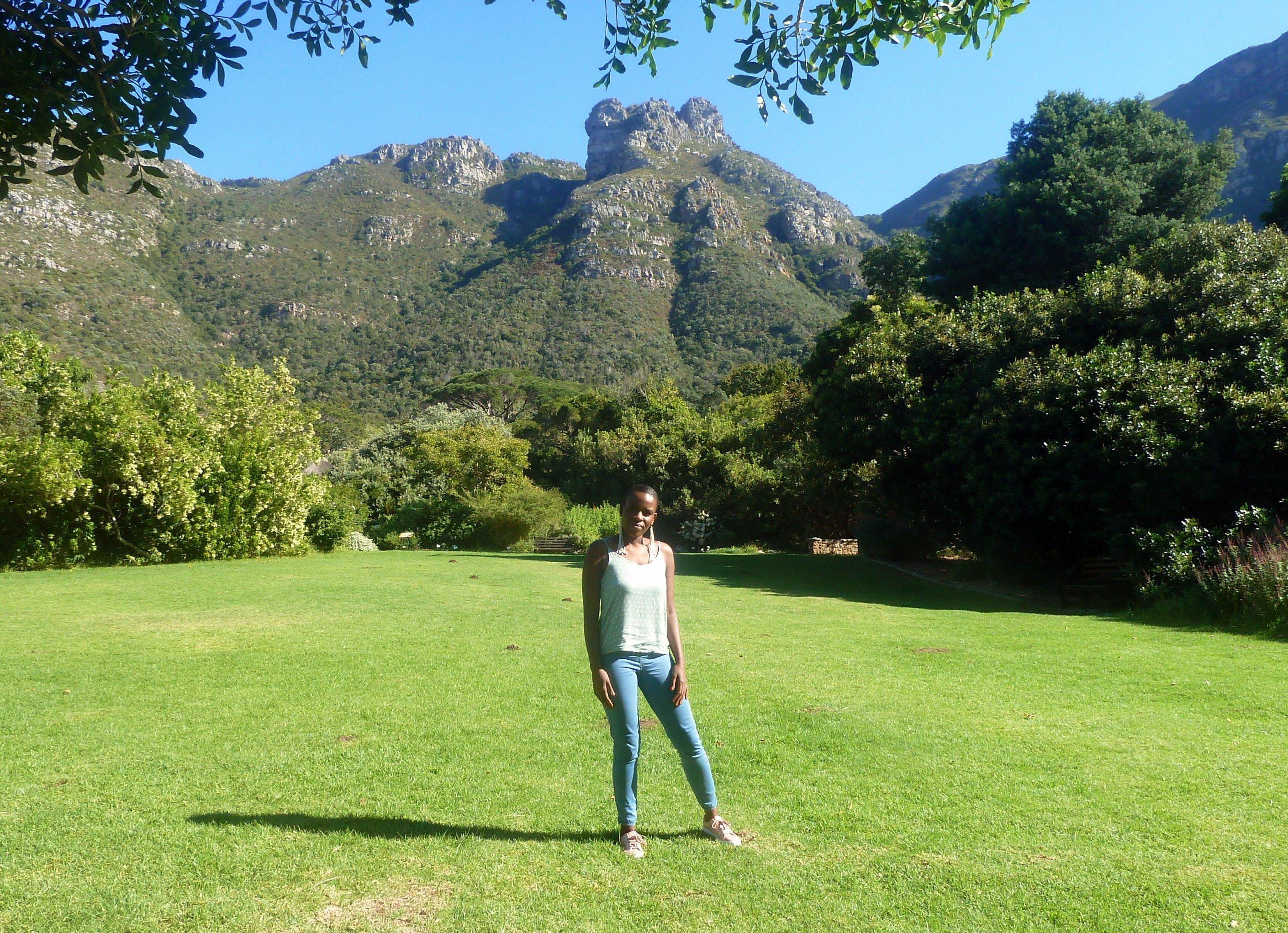 Die Anwältin steht auf einer Wiese im Botanischen Garten von Kapstadt, hinter ihr das Tafelbergmassiv
