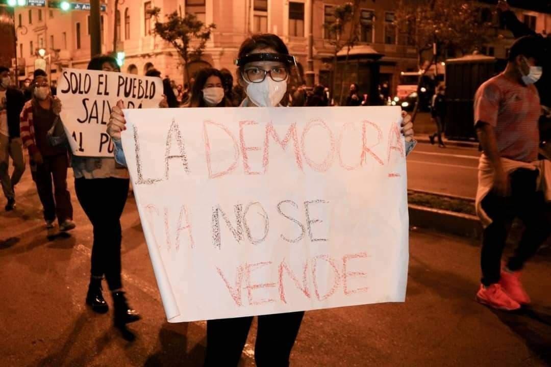 """Junge Frau mit weißem Mundschutz, Brille, trägt ein Plakat vor der Brust, auf dem in spanisch steht: """"La democracia no se vende"""". Die Demokratie lässt sich nicht verkaufen."""