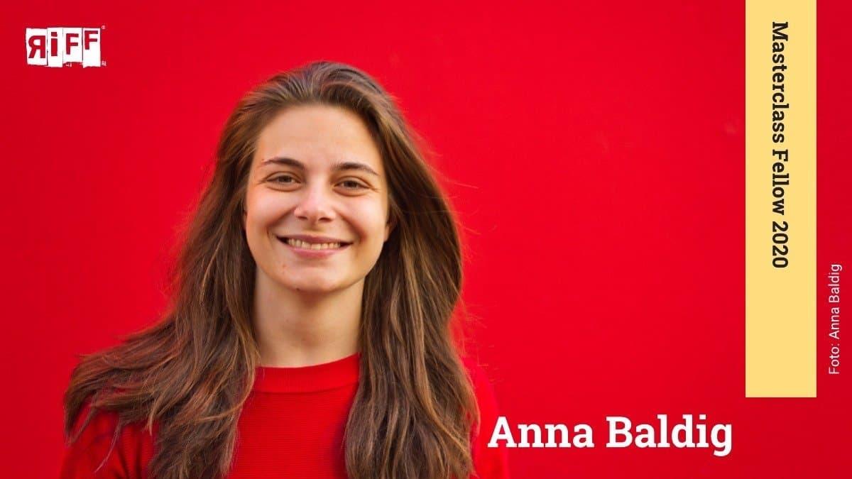 """Junge Frau in rotem Pullover steht lächelnd vor einem roten Hintergrund. Der Name Anna Baldig ist neben ihr zu sehen. An der rechten Seite befindet sich ein Banner mit der Aufschrift """"Masterclass Fellow 2020"""""""
