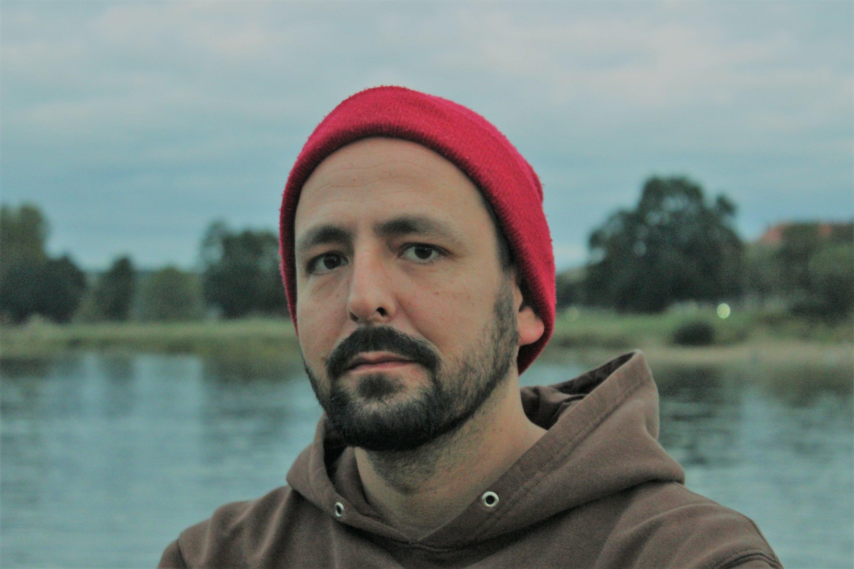 Jan Gehler guckt mit Bart, braunem Hoodie und roter Mütze in die Kamera. Im Hintergrund ein See, am anderen Ufer ein paar Bäume.