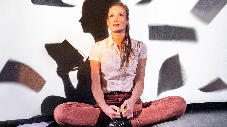 Eine junge Frau mit langen Haaren sitzt nachdenklich im Schneidersitz vor einer weißen Wand. Dahinter sitzt wie ein Schatten eine weitere Schauspielerin. Um sie herum fliegen Notizblätter. Das Bühnenbild von Ansgar Prüwer spiegelt, was Anne Frank sich vorstellt.
