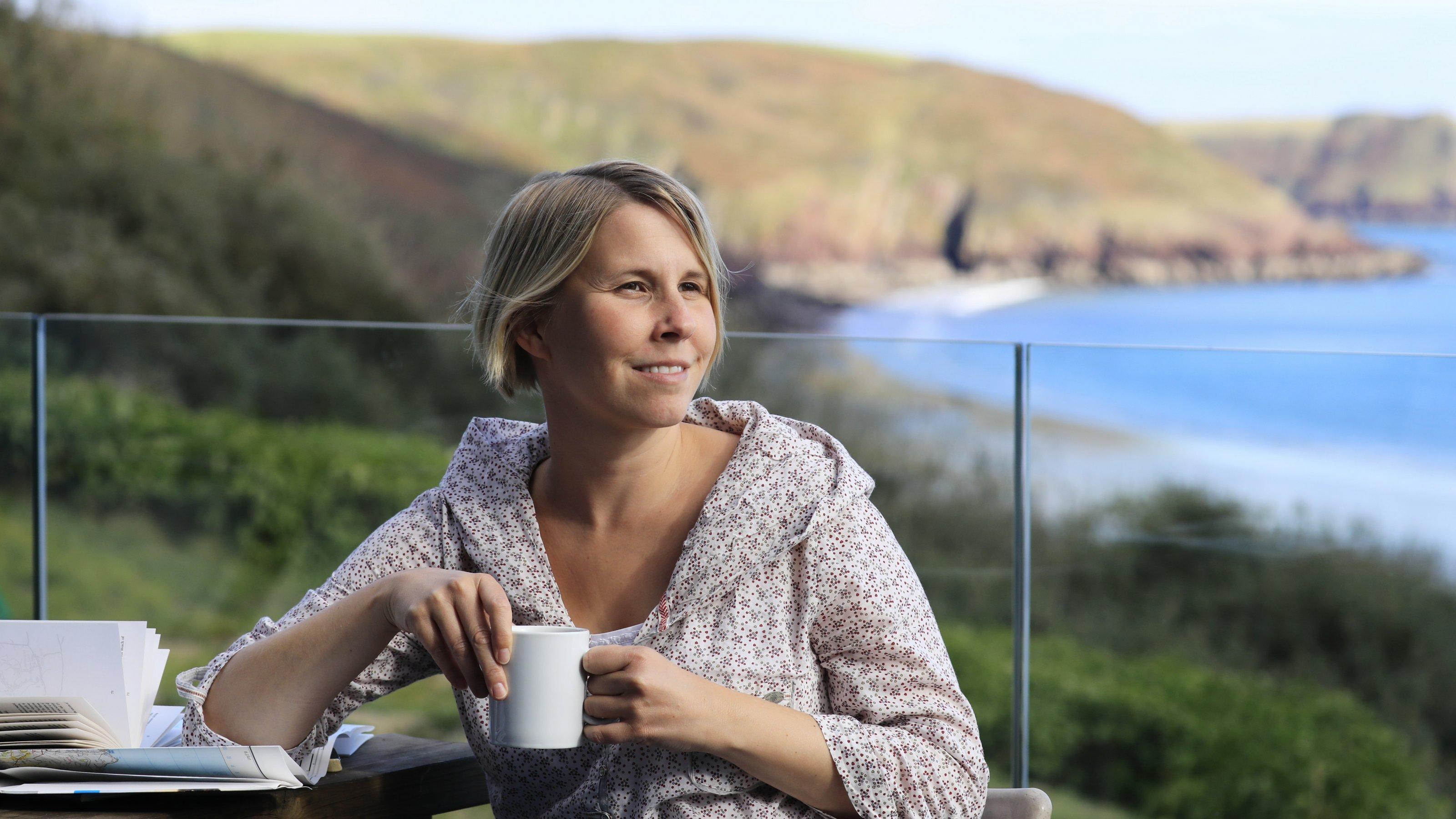 Anne Preger sitzt mit einem Becher in der Hand auf einer Terrasse.