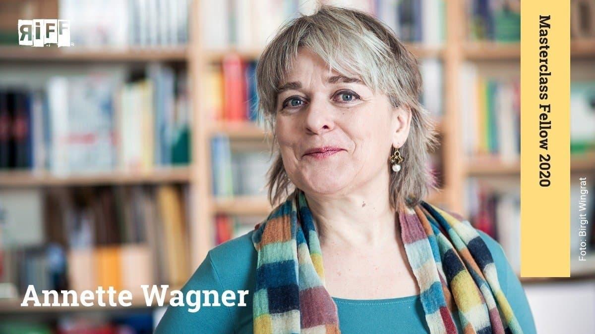 """Eine Frau in türkisem Oberteil und einem mit Quadraten gemusterten Schal steht vor einem Bücherregal. Der Name Annette Wagner ist neben ihr zu sehen. An der rechten Seite befindet sich ein Banner mit der Aufschrift """"Masterclass Fellow 2020""""."""