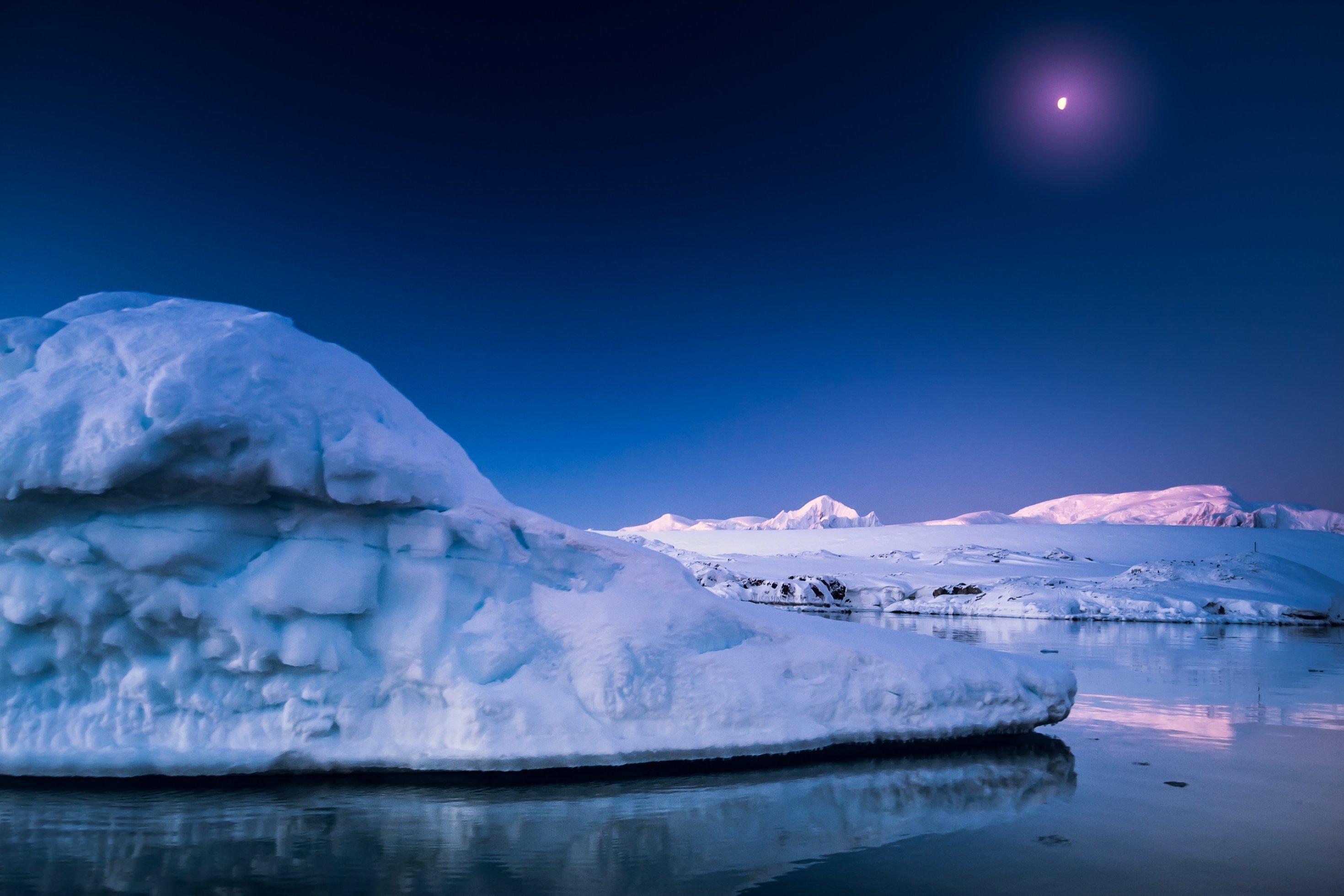 Bild aus der Antarktis. Ein Eisberg schwimmt im Wasser, im Hintergrund sieht man noch größere Berge aus Eis.