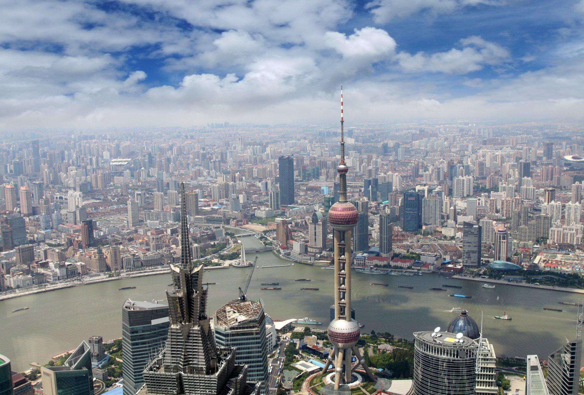 Luftaufnahme einer modernen Großstadt. Durch sie fließt ein großer Fluss, überall sieht man Hochhäuser.