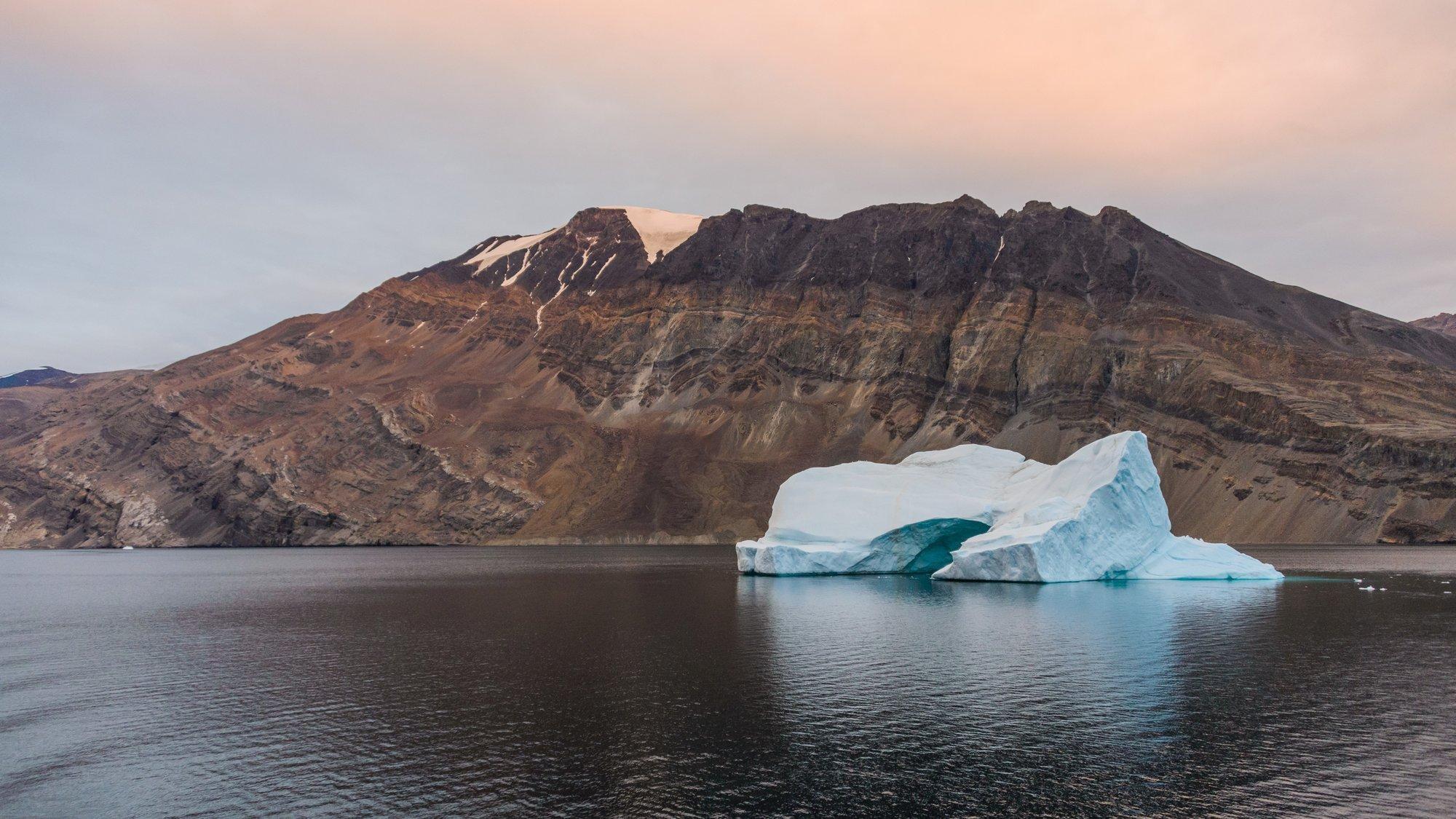 Das Bild zeigt eine grönländische Gebirgslandschaft, mit einem See und einem kleinen Eisberg im Vordergrund.