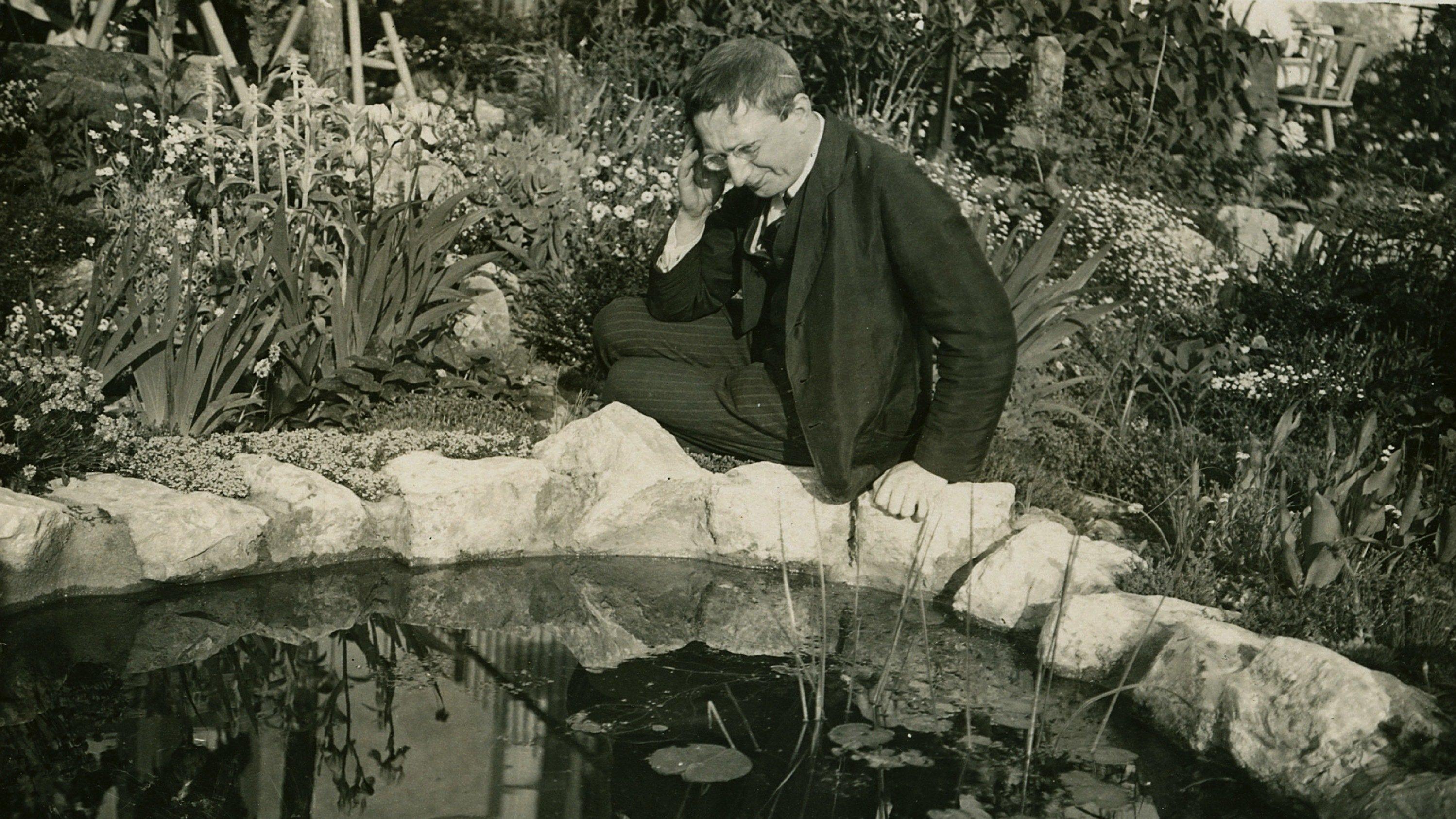 Der Schriftsteller Alfred Döblin sitzt an einem Brunnen.