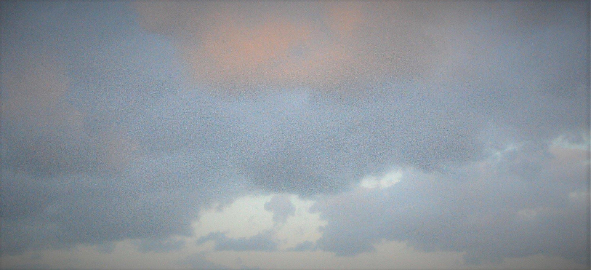 Eine rosa von der restlichen Sonne angestrahlte Wolke am Abendhimmel