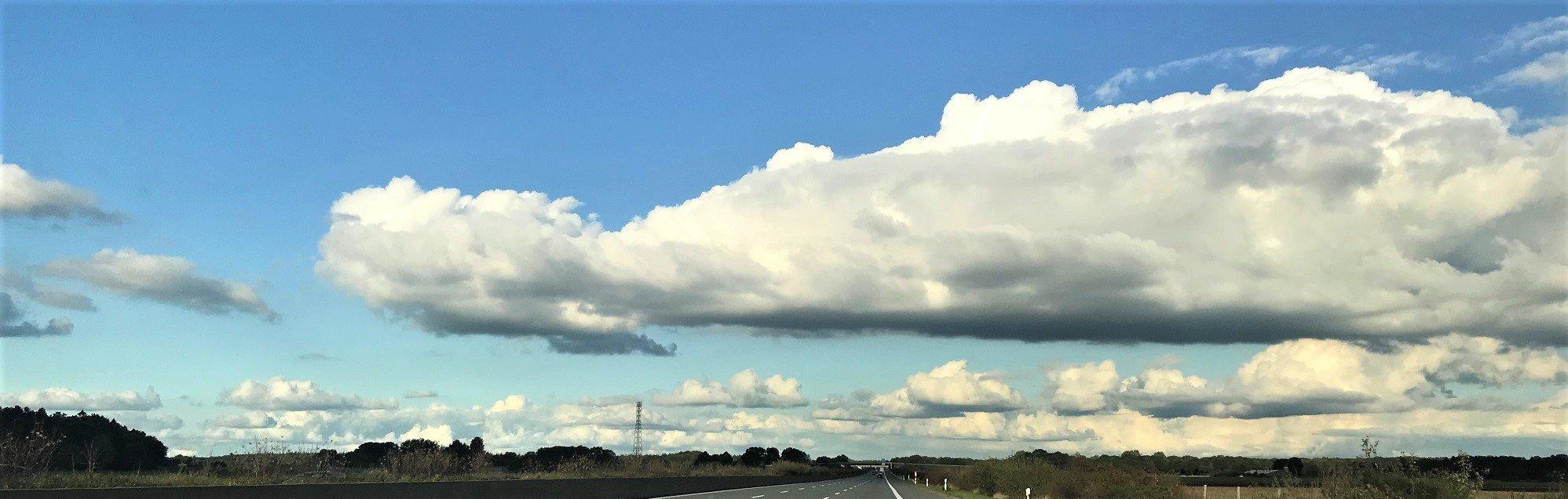 Über eine Landstraße ziehen Wolken hinweg.