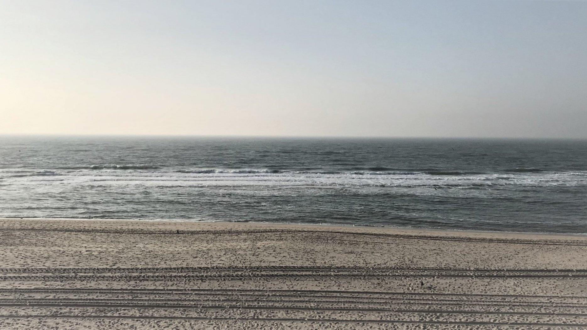 Ein Strand, das Meer und der wolkenlose Himmel darüber.