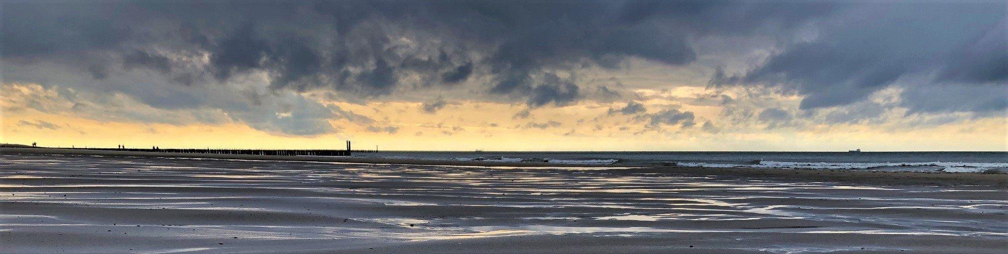 Dunkle Gewitterwolken, darunter ein heller Lichtstreif über aufgewühlter See und einem menschenleeren Strand.