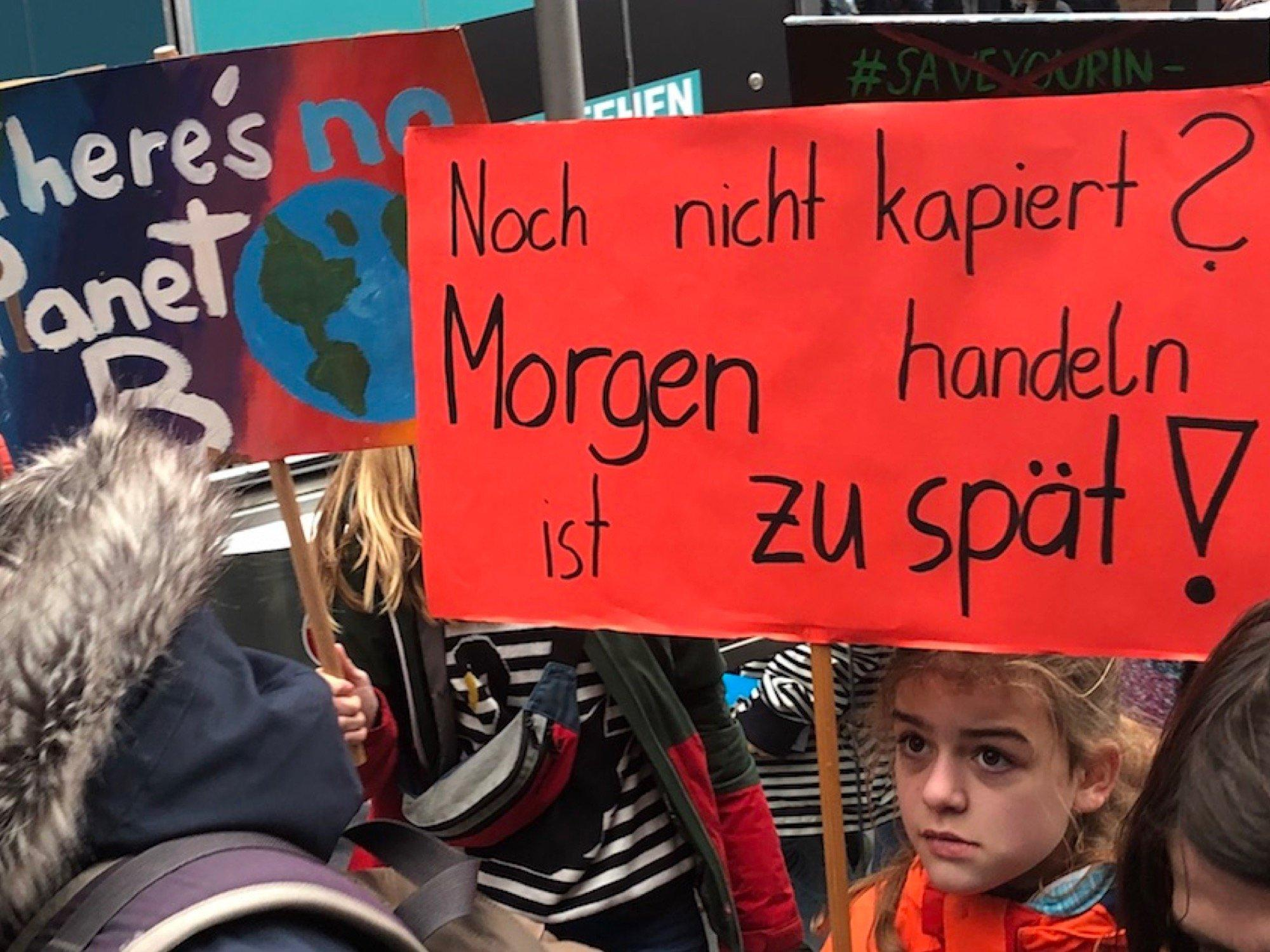 """Einige Demonstranten von Fridays for Future. Auf einem Plakat steht """"Noch nicht kapiert? Morgen handeln ist zu spät!"""""""