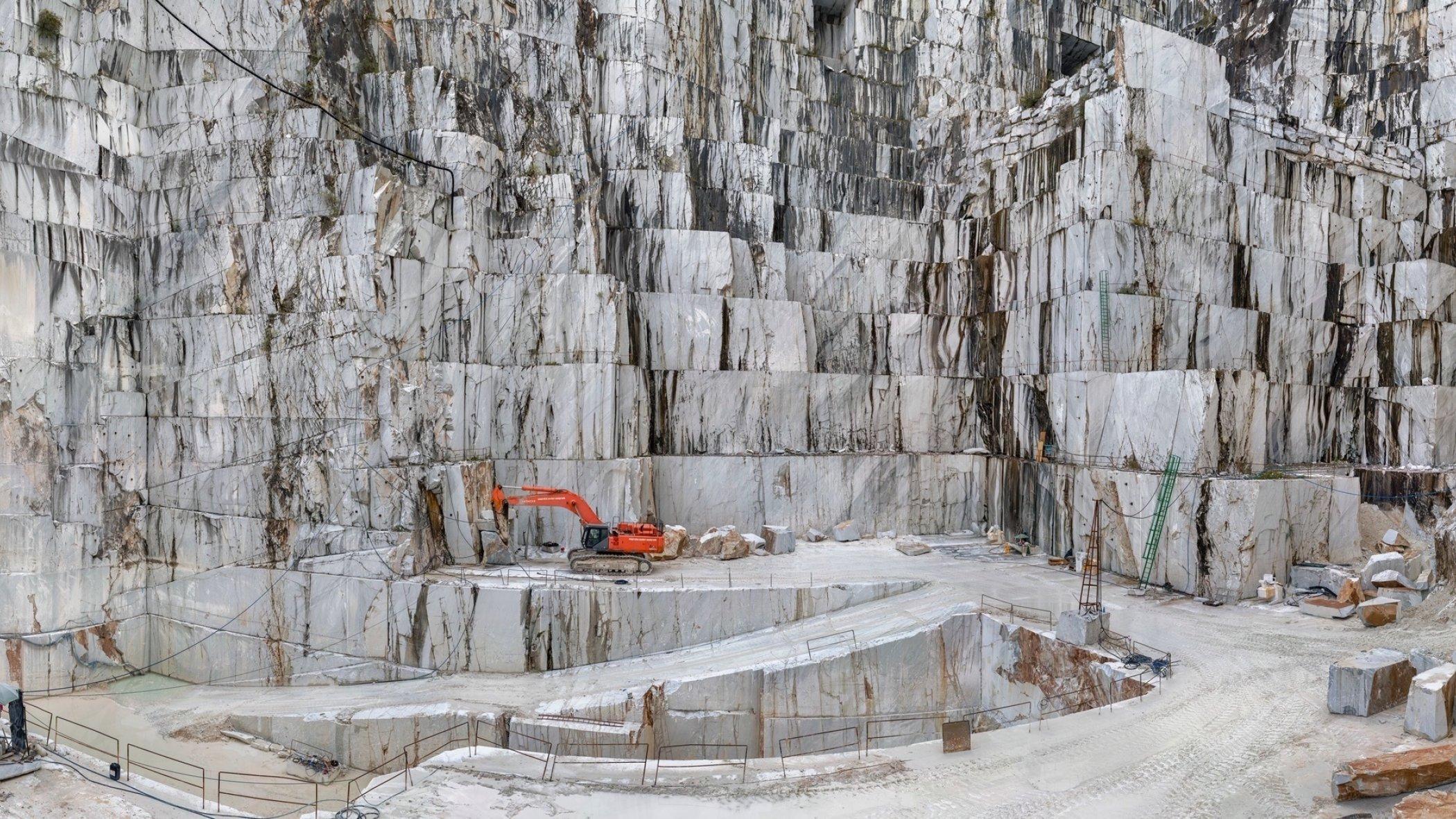Dargestellt ist der Marmorsteinbruch von Carrara – vor der Kulisse riesiger weißer Felswände steht ein Bagger, mit dessen Hilfe Menschen die Gebirgslandschaft verändern.